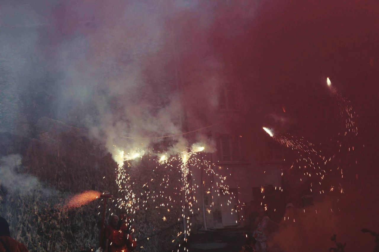 night, smoke - physical structure, burning, crowd, flame, large group of people, celebration, illuminated, real people, outdoors, firework display, arts culture and entertainment, men, audience, forest fire, people
