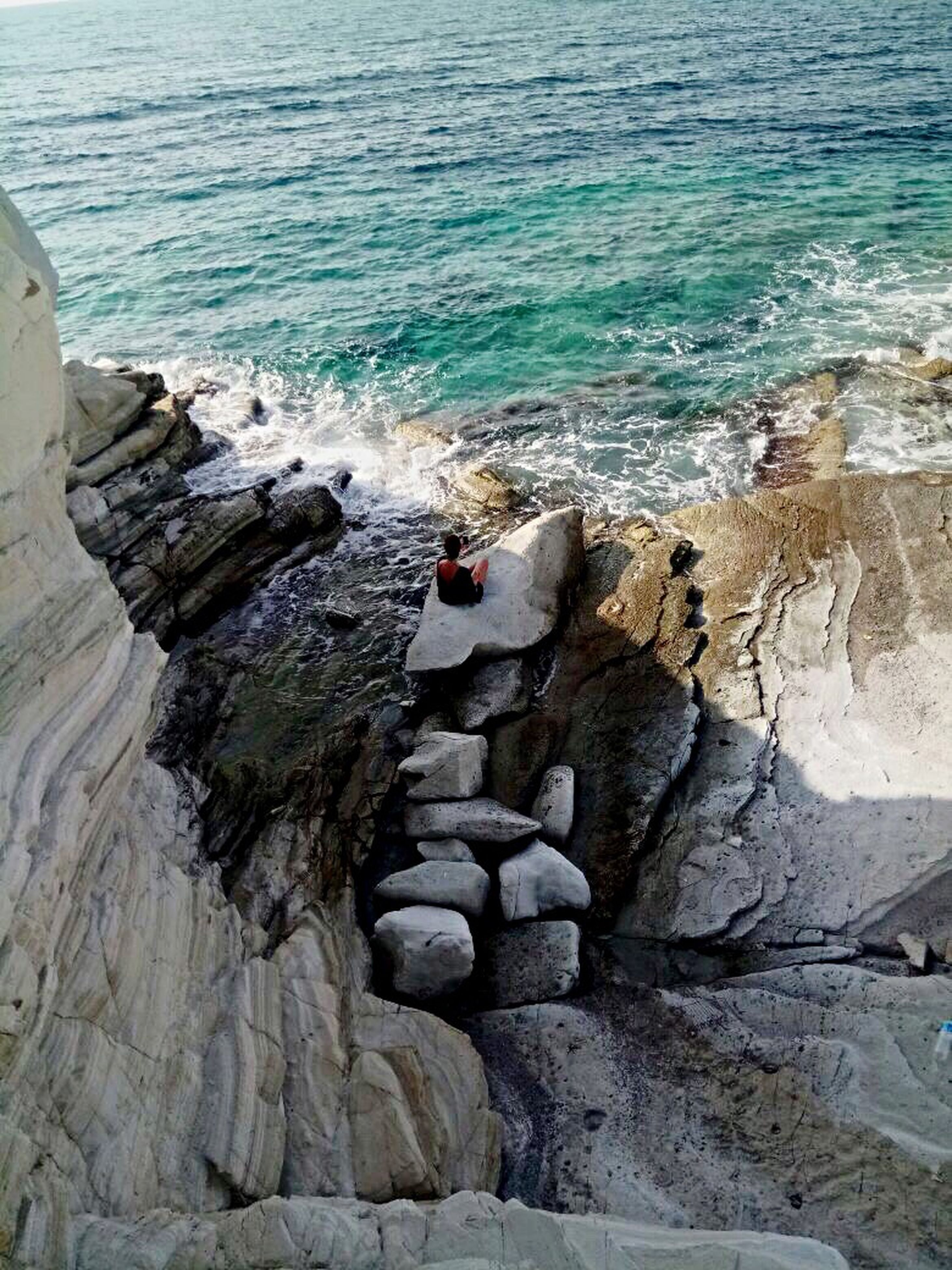 sea, rock - object, water, nature, beauty in nature, day, cliff, scenics, outdoors, wave, horizon over water, one person, people