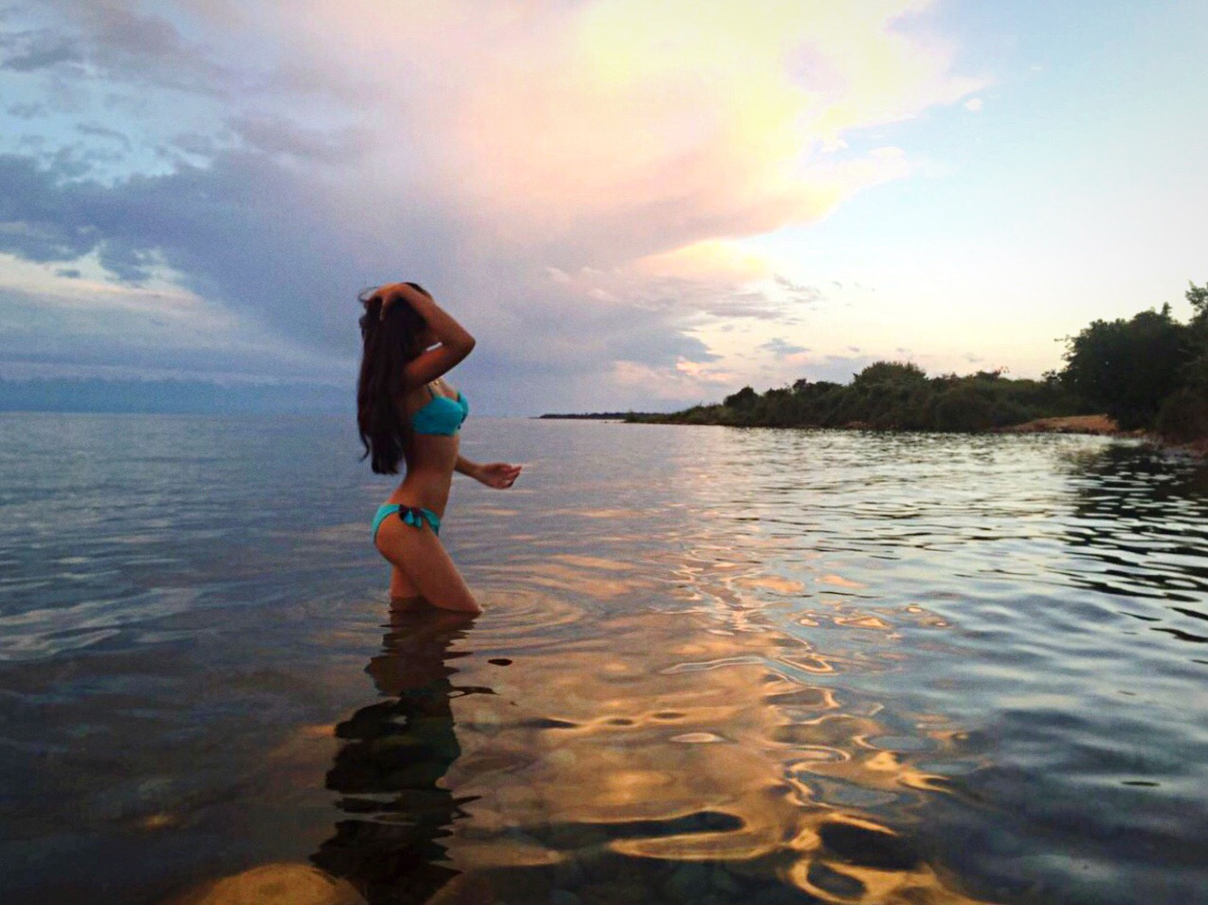 water, full length, lifestyles, sky, sunset, leisure activity, scenics, sea, side view, cloud - sky, childhood, person, beauty in nature, fun, nature, casual clothing, tranquility, tranquil scene, vacations, carefree, enjoyment, waterfront, non-urban scene