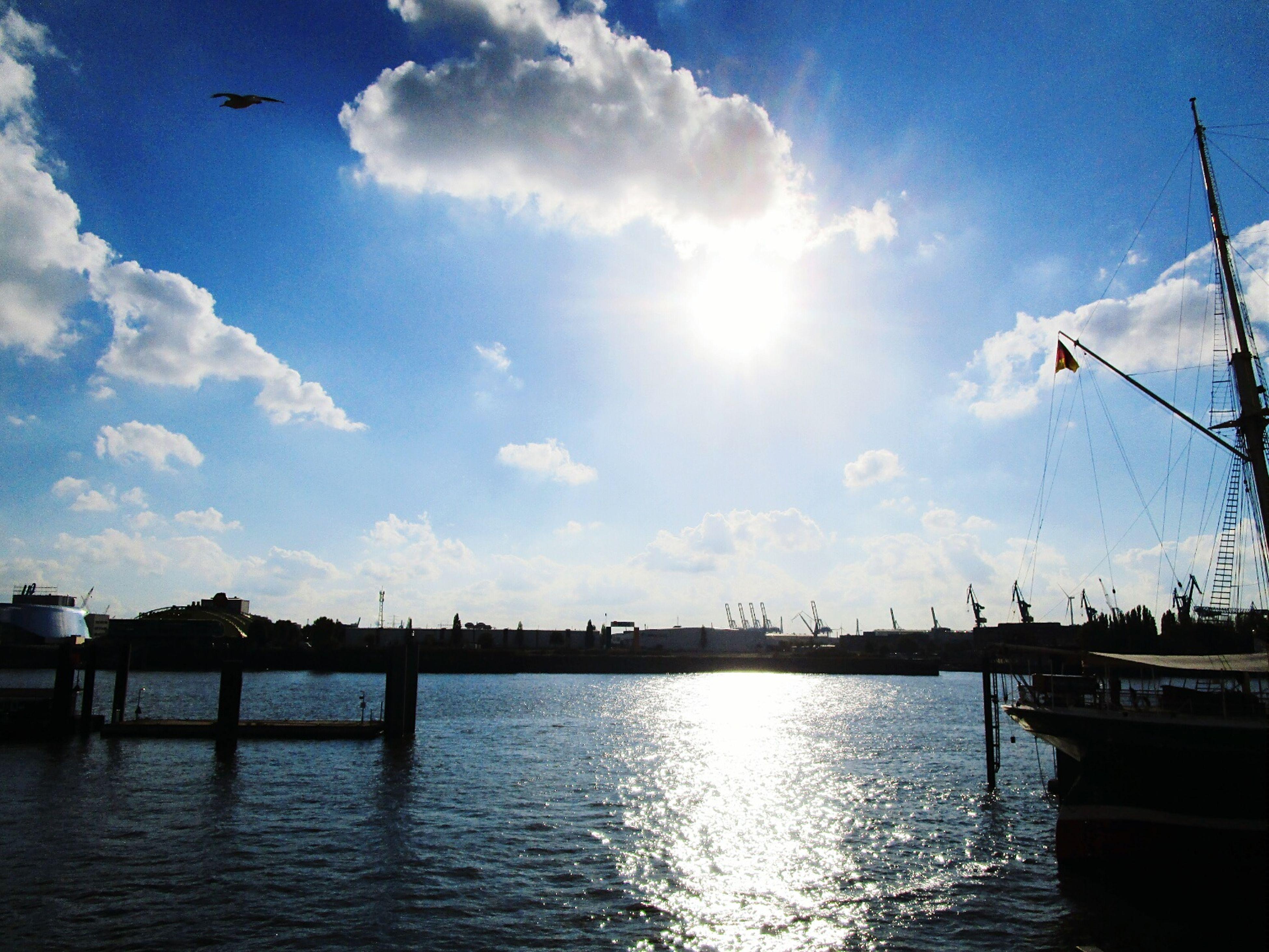 water, sky, sea, waterfront, sun, transportation, cloud - sky, sunlight, nautical vessel, harbor, mode of transport, bird, cloud, sunbeam, reflection, blue, river, nature, built structure, silhouette