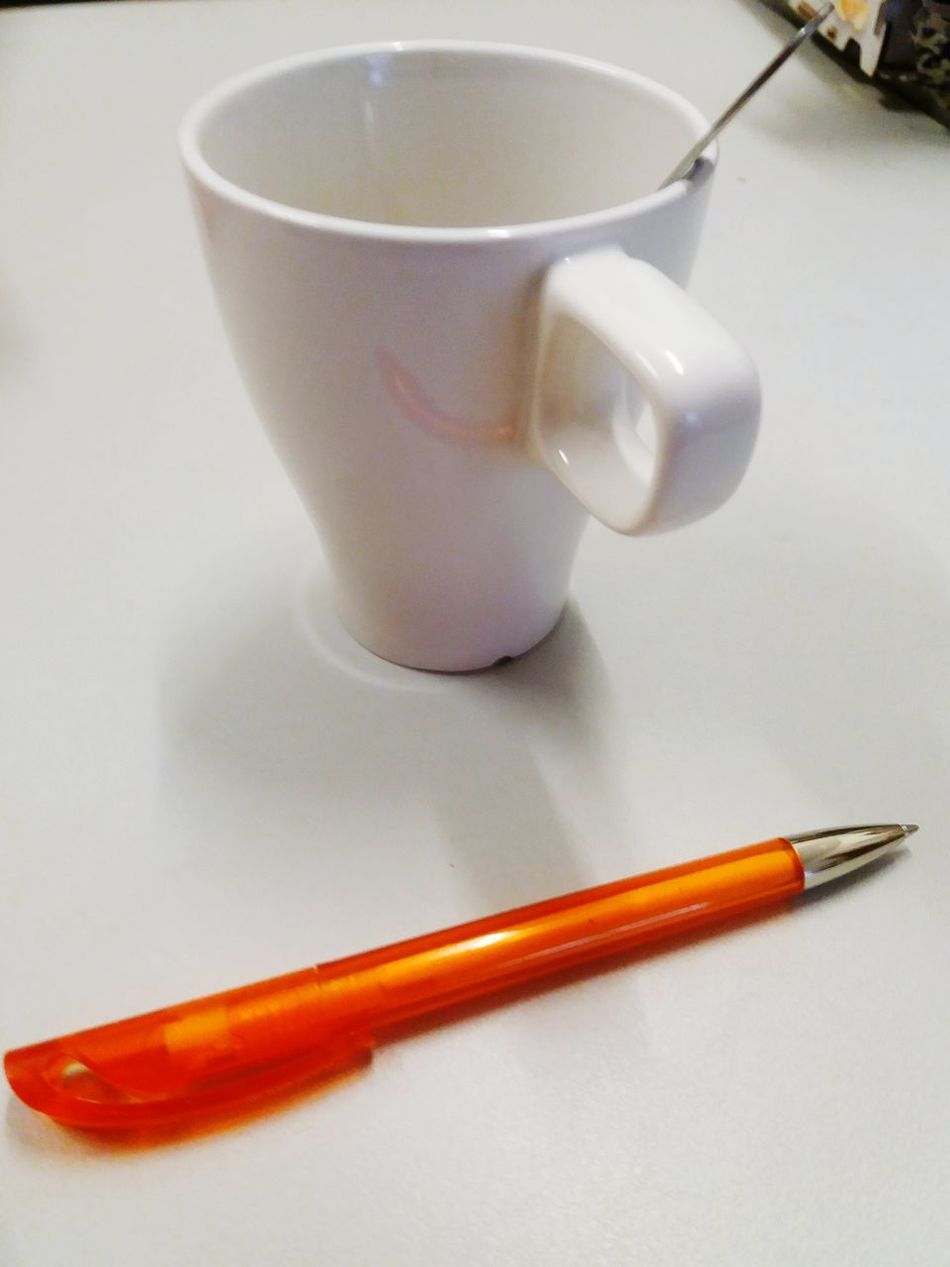 A white cup and a ball point pen No People Close-up Indoors  Writing And Relaxing Writing And Coffee Writing Dishware Tableware Crockery Orange Ball Point Pen Orange Color Ball Point Pen Pen Cuppa Cup Spoon Work