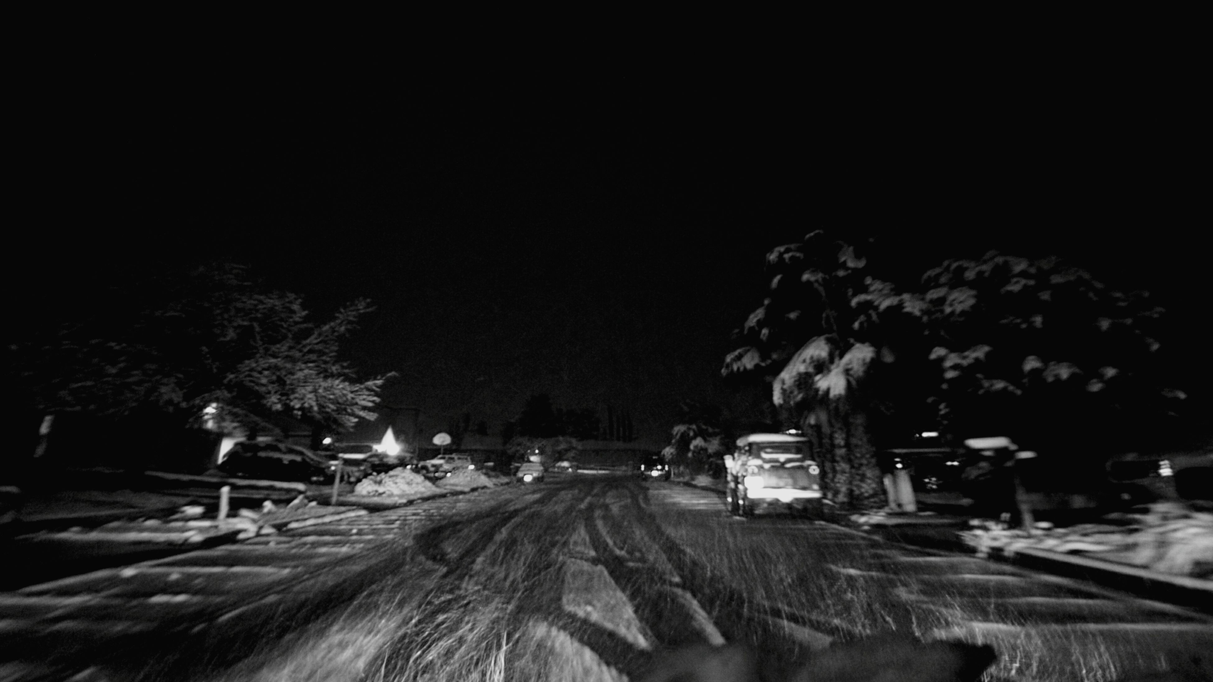 transportation, road, tree, snow, the way forward, winter, car, land vehicle, night, mode of transport, street, cold temperature, clear sky, high angle view, railroad track, outdoors, diminishing perspective, sky, nature, illuminated