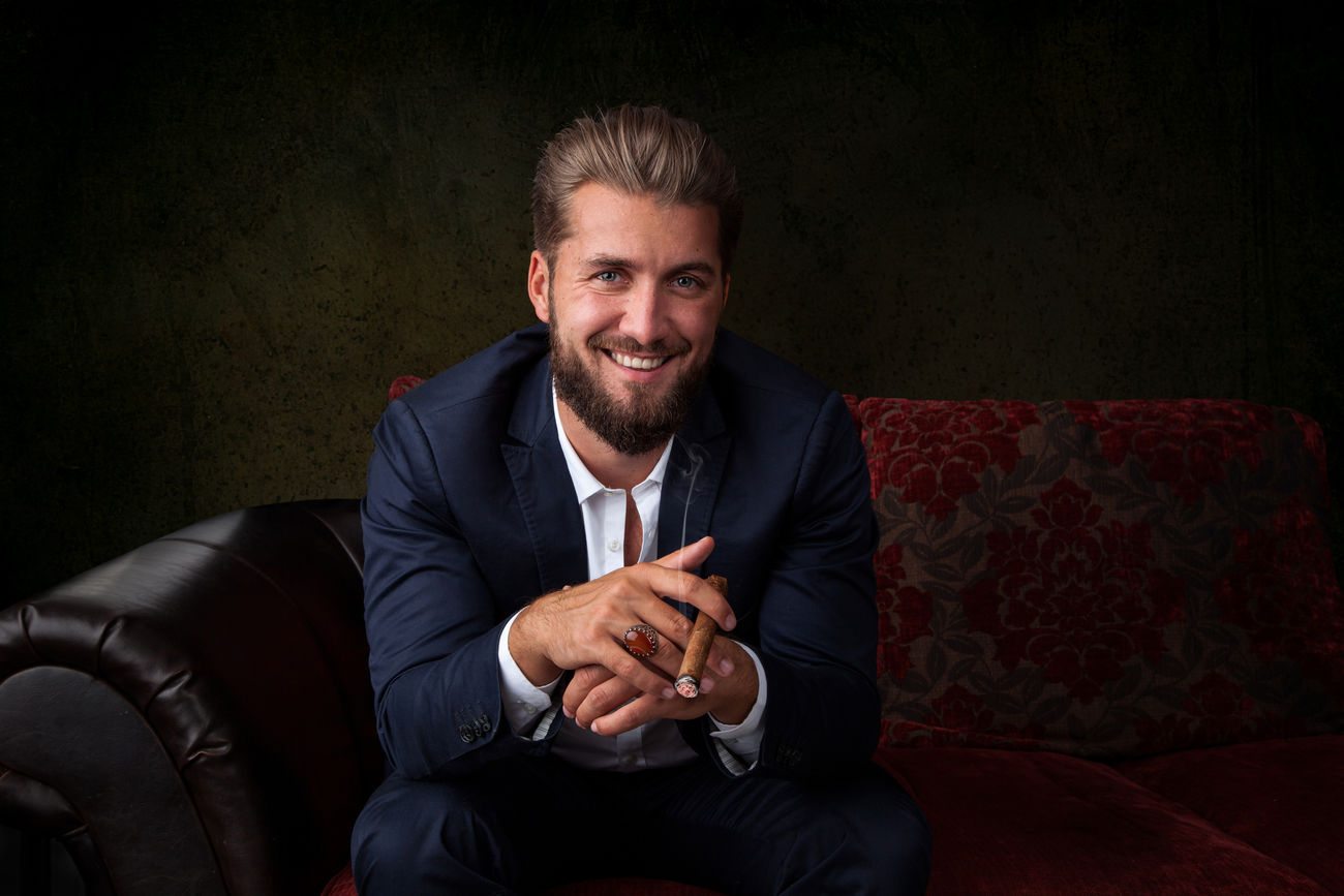 Portrait of an attractive man on a couch with a cigar Attractive Background Beard Black Businessman Cigar Couch Elegant Handsome Holding Lifestyle Luxury Mafia  Manager Model Muslime One People Person Relax Sit Smile Smoke Successful Suit