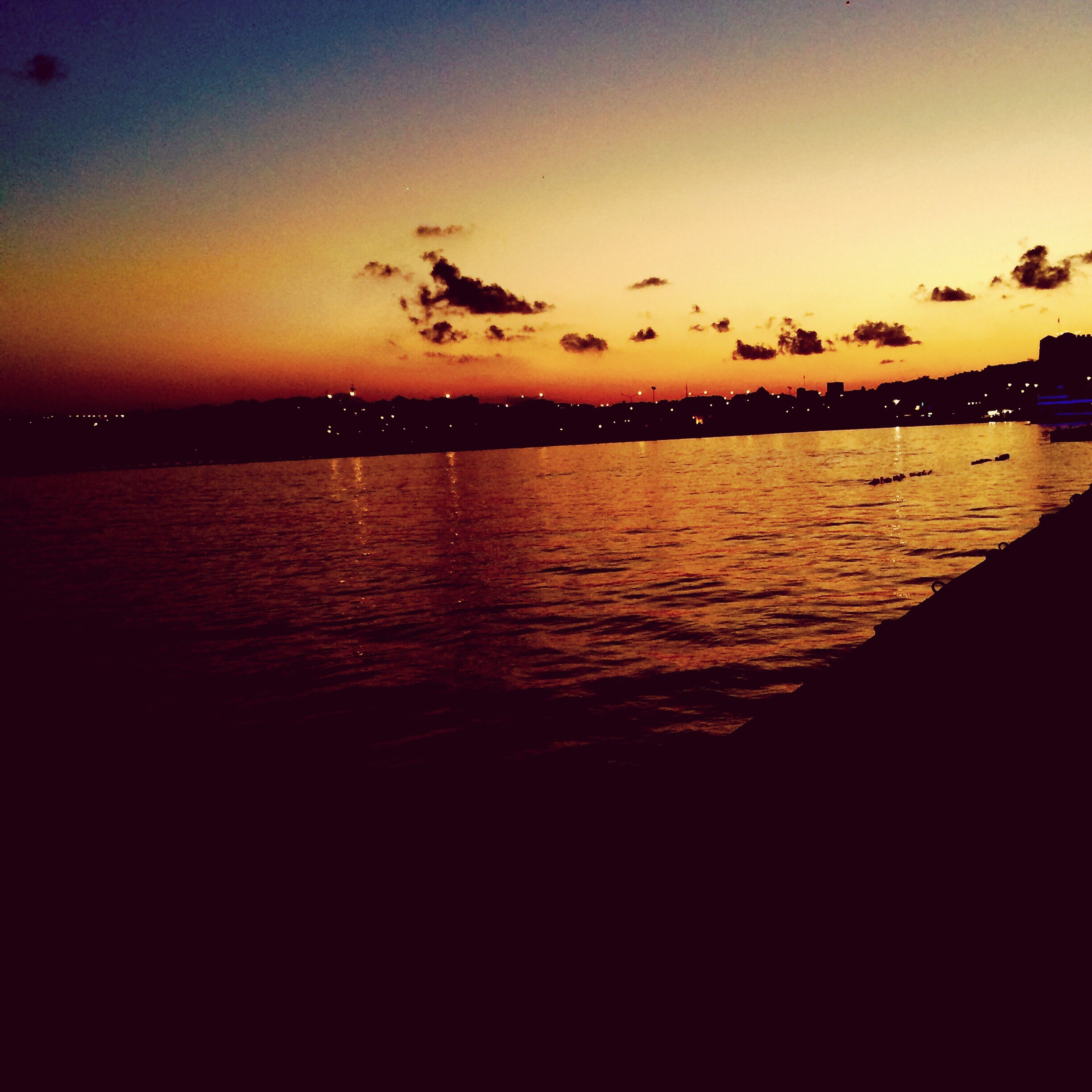 sunset, tranquil scene, scenics, water, tranquility, dusk, beauty in nature, sky, idyllic, nature, majestic, orange color, remote, non-urban scene, cloud - sky, dark, calm, sea, vibrant color, mountain, flying, no people, atmosphere, waterfront, seascape, distant, dramatic sky, atmospheric mood