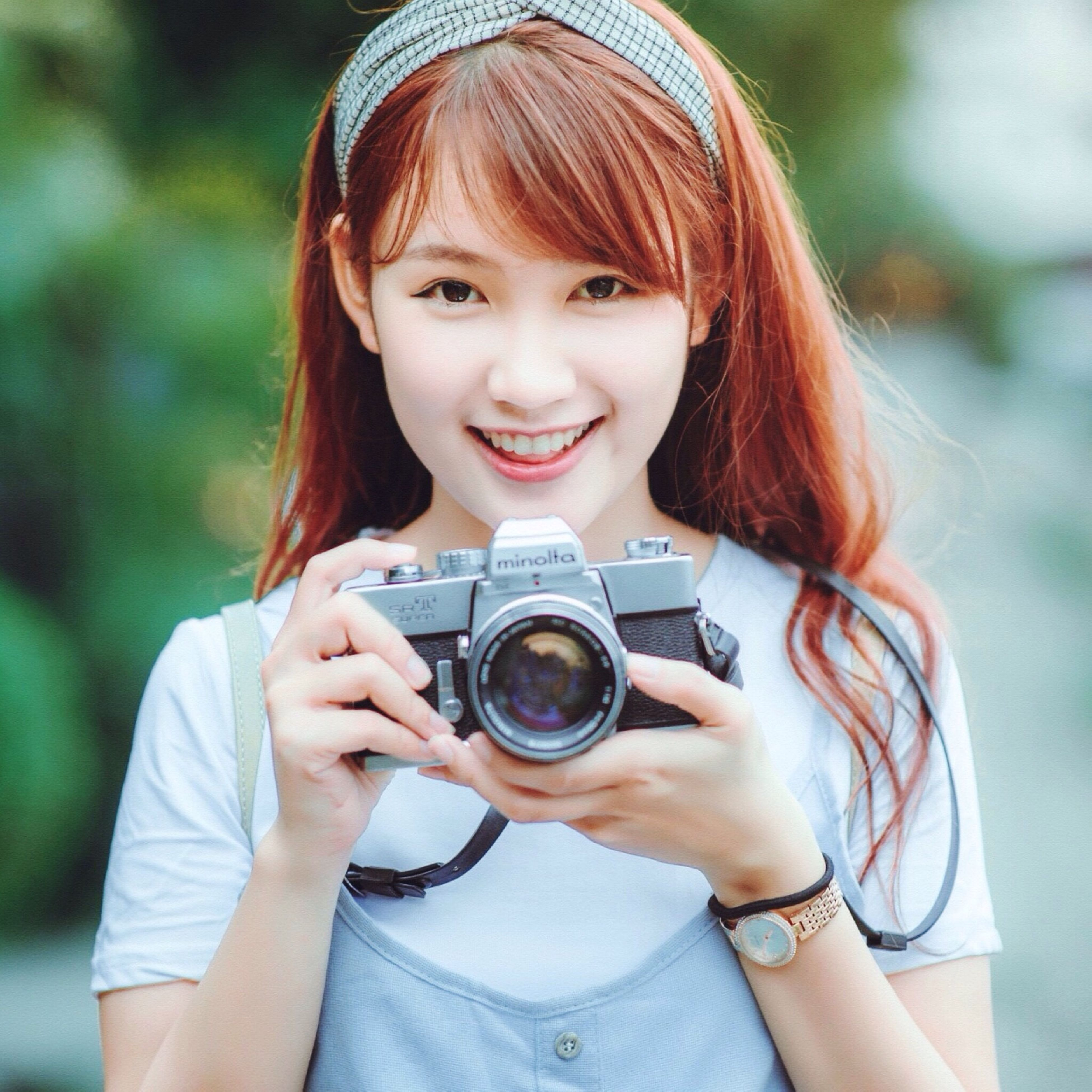 lifestyles, leisure activity, holding, person, sunglasses, looking at camera, casual clothing, young adult, portrait, focus on foreground, front view, photography themes, smiling, technology, photographing, refreshment, happiness, camera - photographic equipment