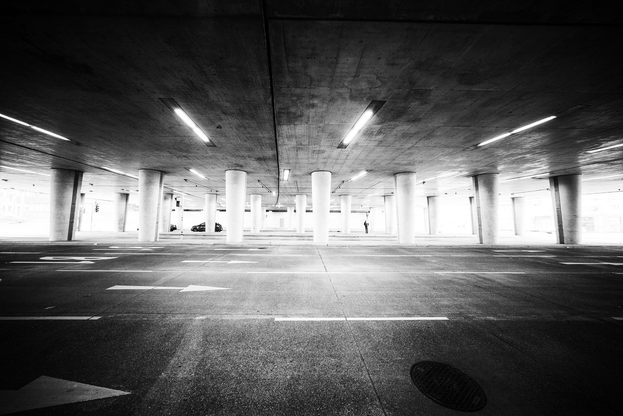 parking lot, illuminated, indoors, ceiling, empty, built structure, no people, architecture, architectural column, parking garage, underground, basement, day