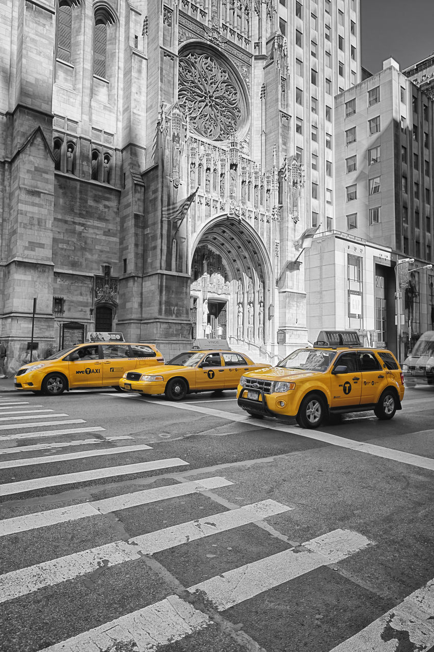 yellow taxi, taxi, car, yellow, transportation, architecture, arch, city street, city, building exterior, street, built structure, speed, history, day, outdoors, travel destinations, no people