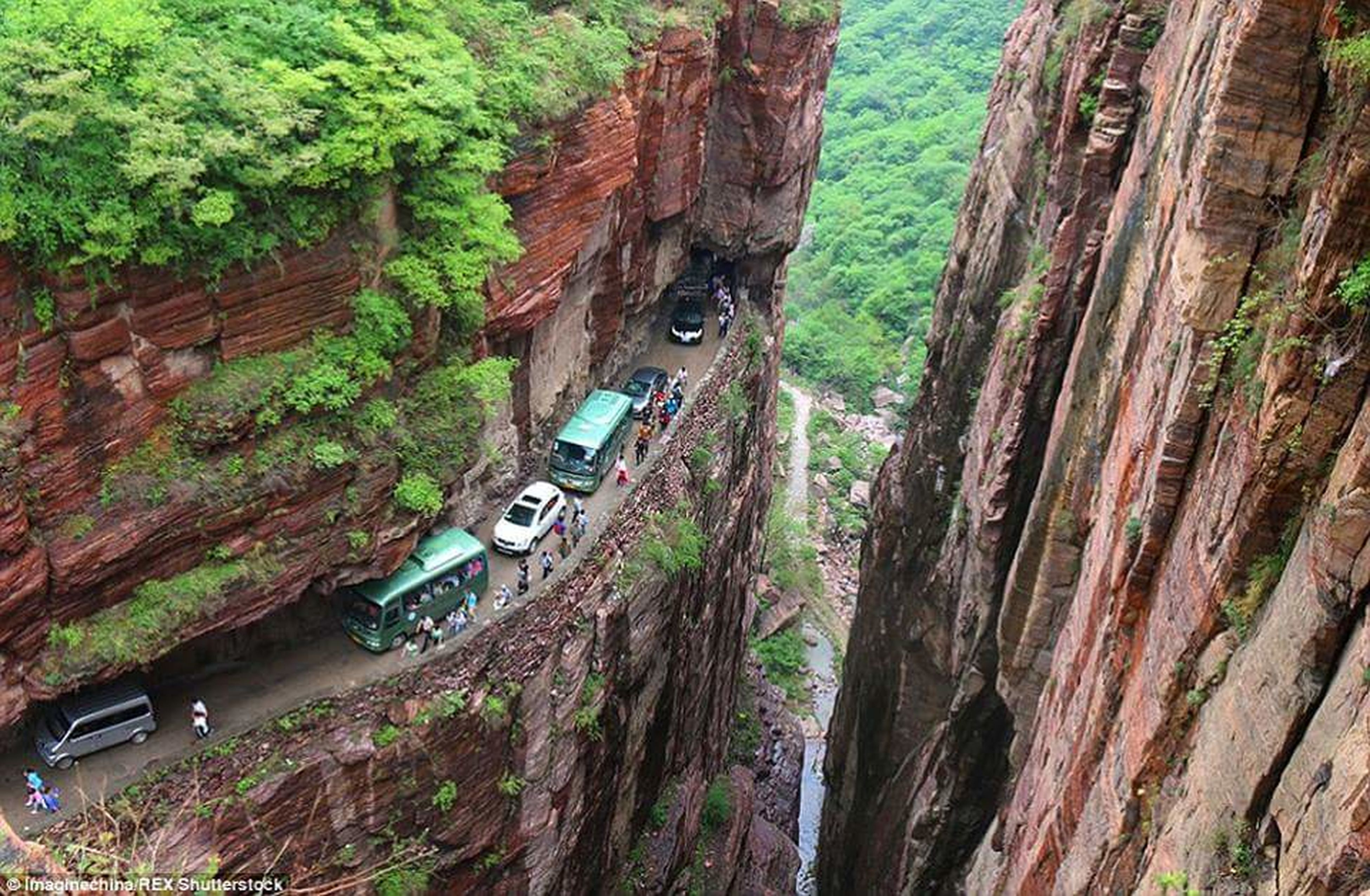 transportation, tree, forest, nature, high angle view, mode of transport, road, green color, mountain, growth, day, tranquility, travel, rock formation, outdoors, car, beauty in nature, rock - object, lush foliage, tranquil scene