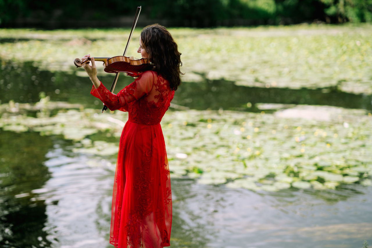 A violinist plays music amidst nature. Adult Day Holding Lake Music Musical Instrument Musician Nature One Person Outdoors People Real People Red Standing Violin Water Young Adult Young Women