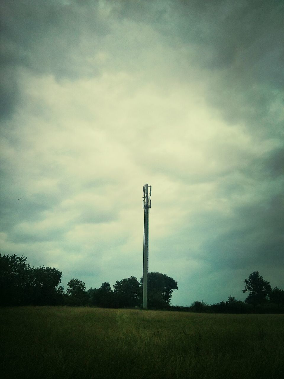 Communications Tower On Grassy Field Against Cloudy Sky