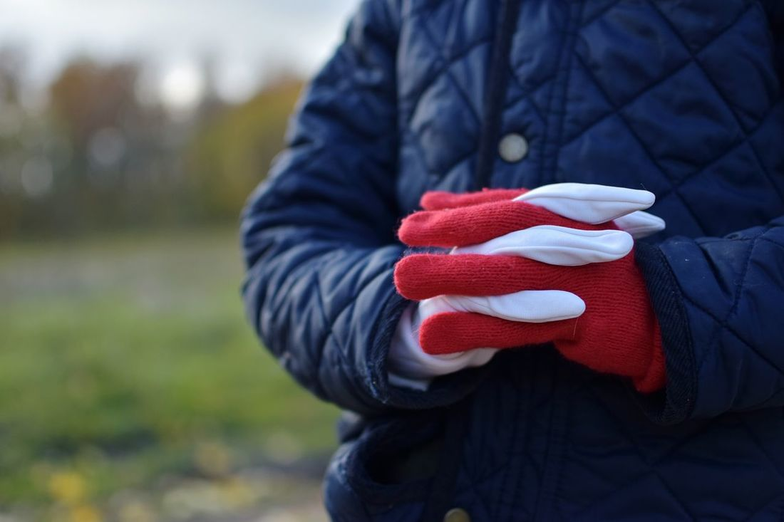 One Person Warm Clothing People Outdoors Human Body Part Winter Child Cold Temperature Red Human Hand Day Close-up Childhood Nature Gloves Different Colors White Red Gloves White Glove Casual Clothing Autumn Red And White White And Red Fashion Stories