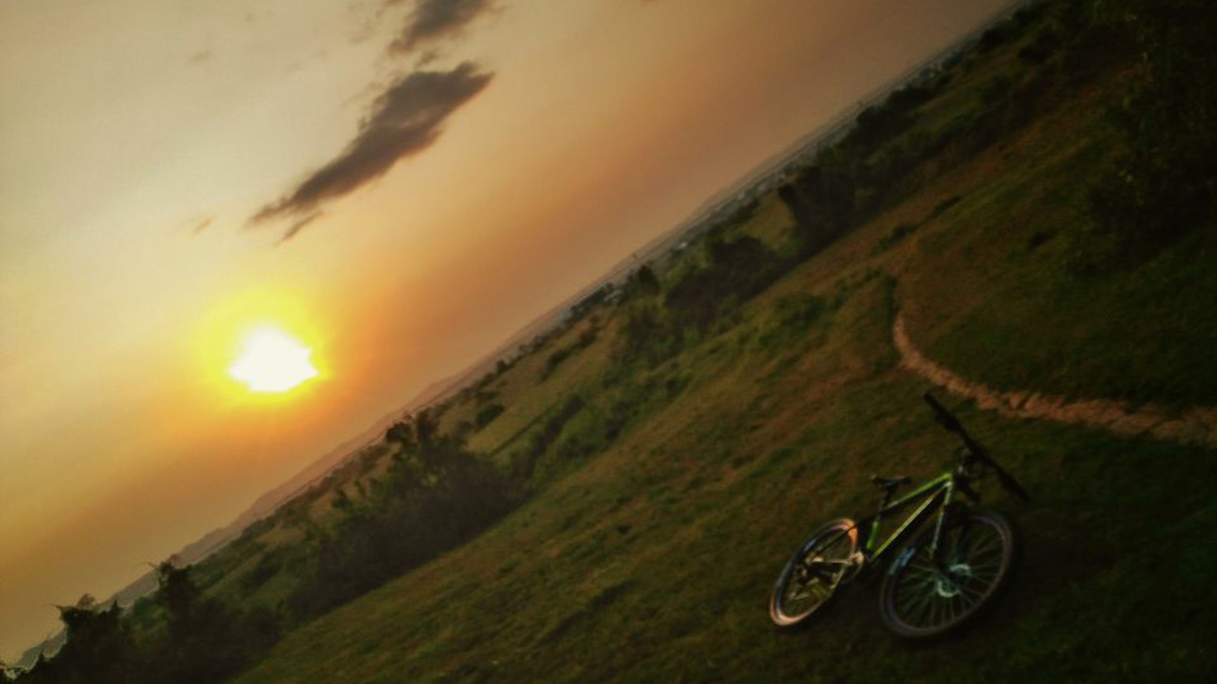 bicycle, cycling, sunset, scenics, transportation, tranquil scene, landscape, nature, no people, outdoors, pedal, mountain, wheel, grass, mountain bike, sky, day, beauty in nature