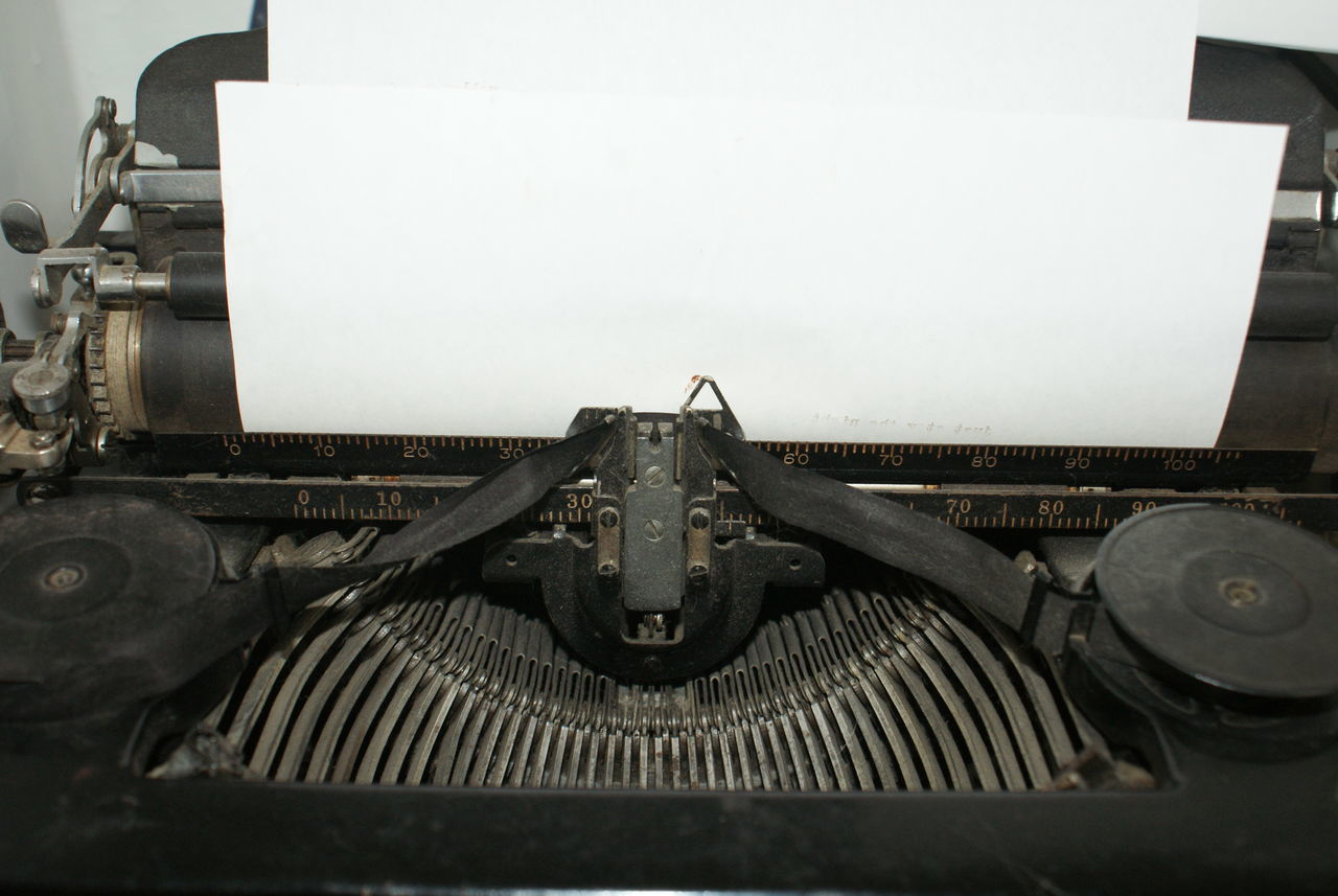 An old manual typewriter showing the ribbon and key arms has a blank sheet of paper ready for type. Antique Author Blackandwhite Blank Paper Close-up Day Lieblingsteil Manual Typewriter No People Ready To Write Space For Copy Typewriter Typing Unedited Photo White Paper Writing