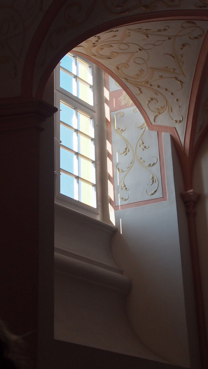 Low Angle View Of Designs On Wall By Window