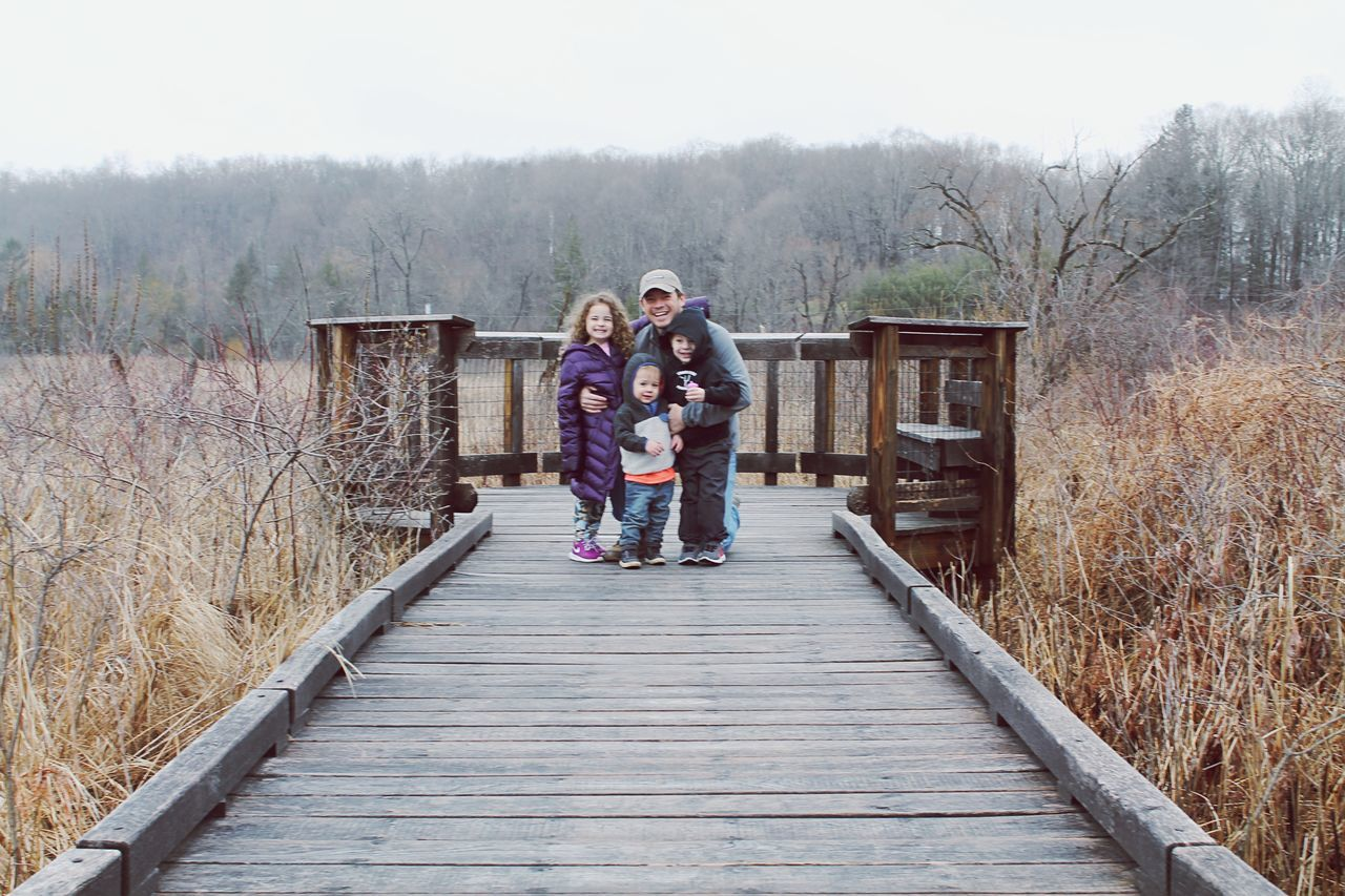 full length, real people, two people, leisure activity, tree, girls, togetherness, day, front view, outdoors, casual clothing, childhood, lifestyles, bonding, looking at camera, standing, bare tree, nature, built structure, grass, building exterior, portrait, footbridge, architecture, sky, warm clothing, young adult, people