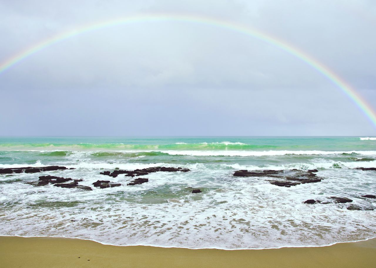 Scenic View Of Rainbow In Sea Against Sky