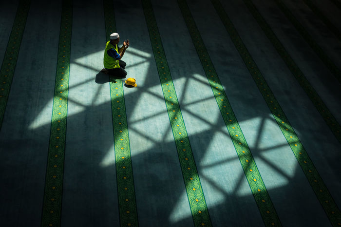 A worker takes a break to perform his prayer Design Helmet Light And Shadow Man Mosque Prayer Praying Safety Helmet Worker Yellow Yellow Helmet