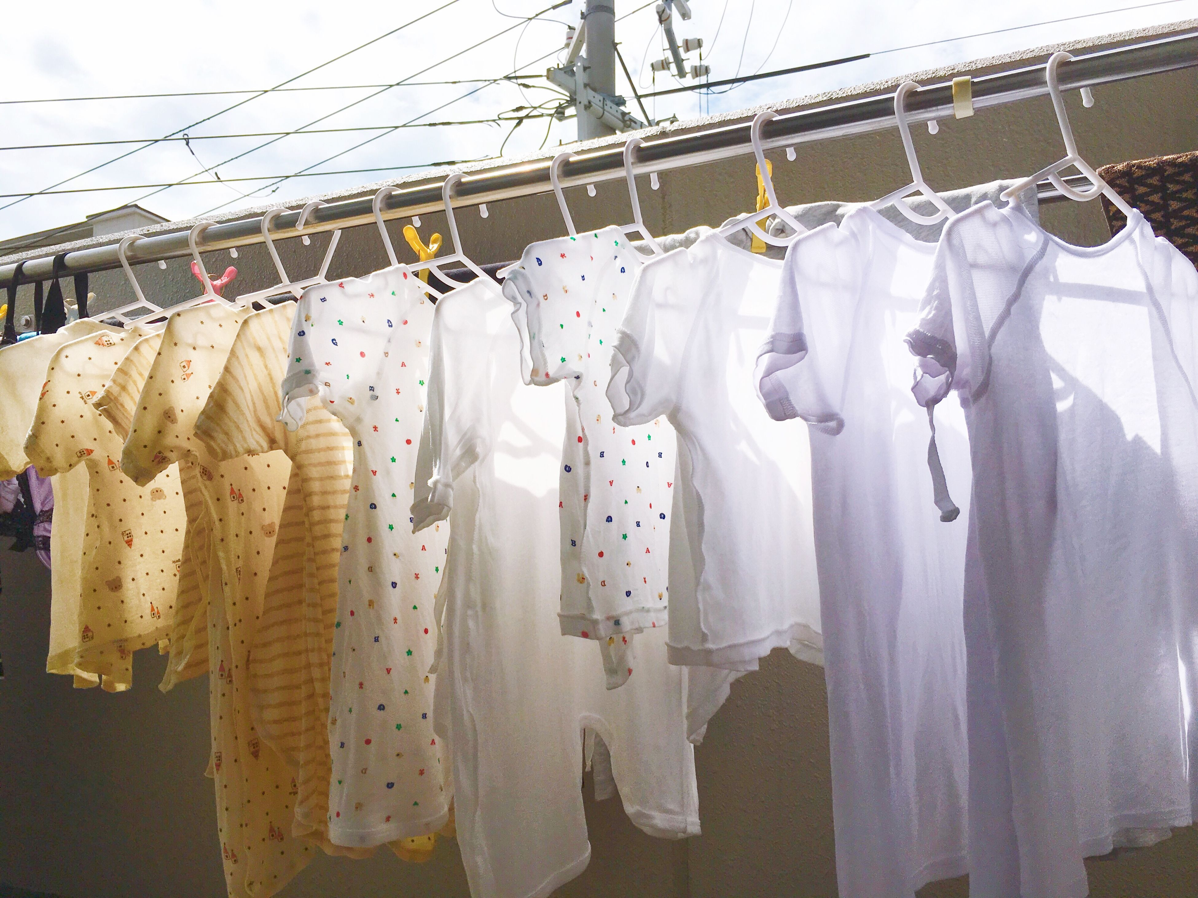 hanging, variation, clothing, in a row, for sale, large group of objects, choice, collection, display, abundance, laundry, retail display, clothes, retail, no people, day, sky