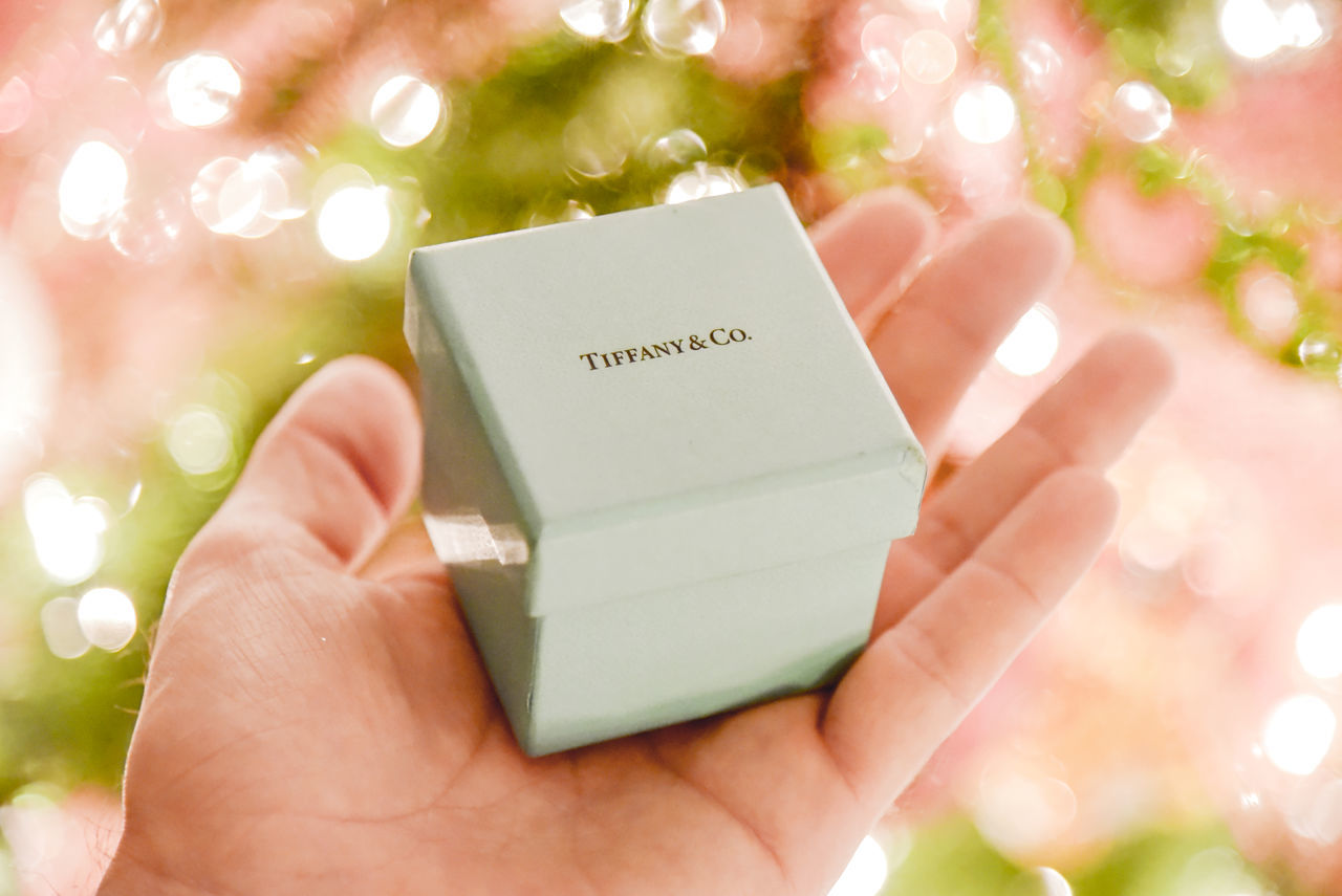 Tiffany gift box in hand holiday lights. Bling Bokeh Box Christmas Close-up Day Diamonds Gift Giving Holding Human Body Part Human Hand Investing Jewelry Lights Man One Person Outdoors People Personal Perspective Propose Text Tiffany&Co. Wealth Wedding