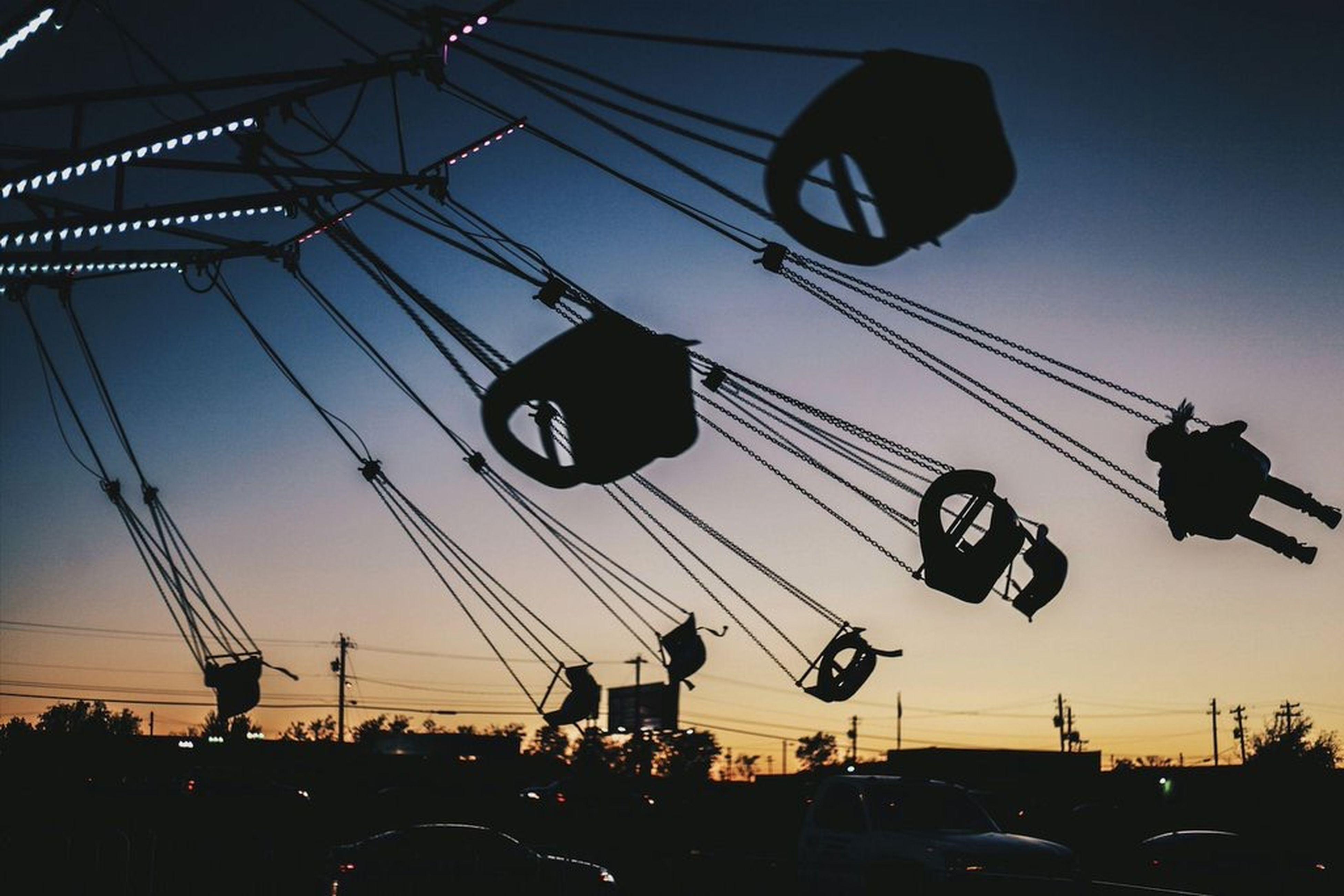 transportation, silhouette, low angle view, sunset, mode of transport, sky, power line, large group of people, leisure activity, cable, men, amusement park, dusk, lifestyles, enjoyment, car, person, arts culture and entertainment, land vehicle