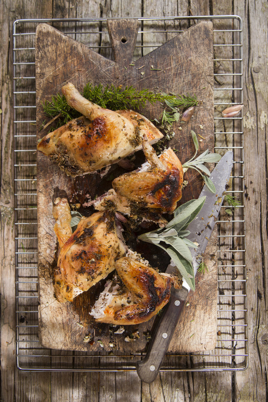 Directly Above Shot Of Roast Chicken On Cutting Board With Rack Over Wooden Table