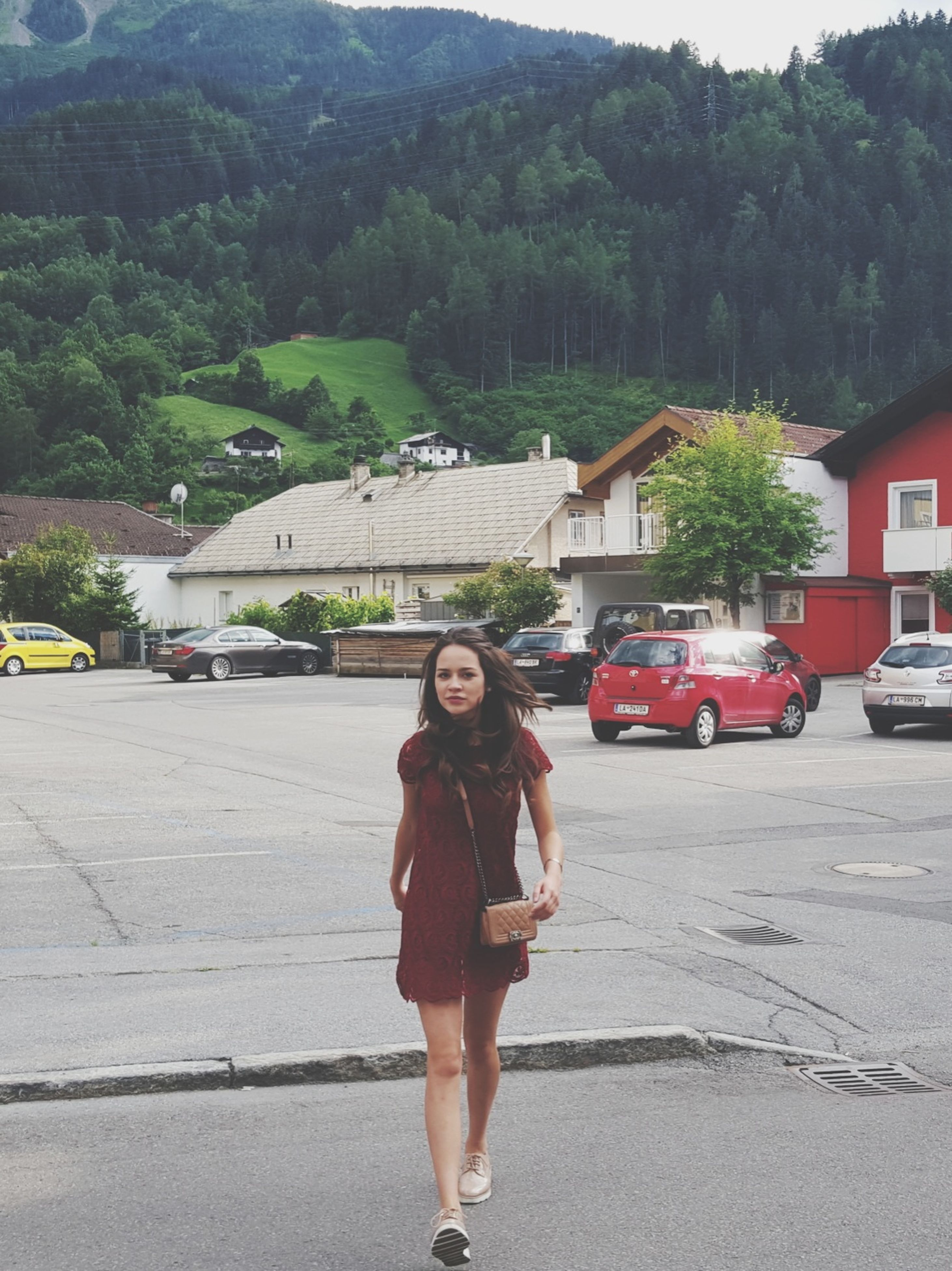 full length, architecture, street, young adult, leisure activity, young women, casual clothing, smiling, lifestyles, built structure, person, building exterior, standing, front view, car, long hair, portrait, tree, mountain, in front of, medium-length hair, day, outdoors