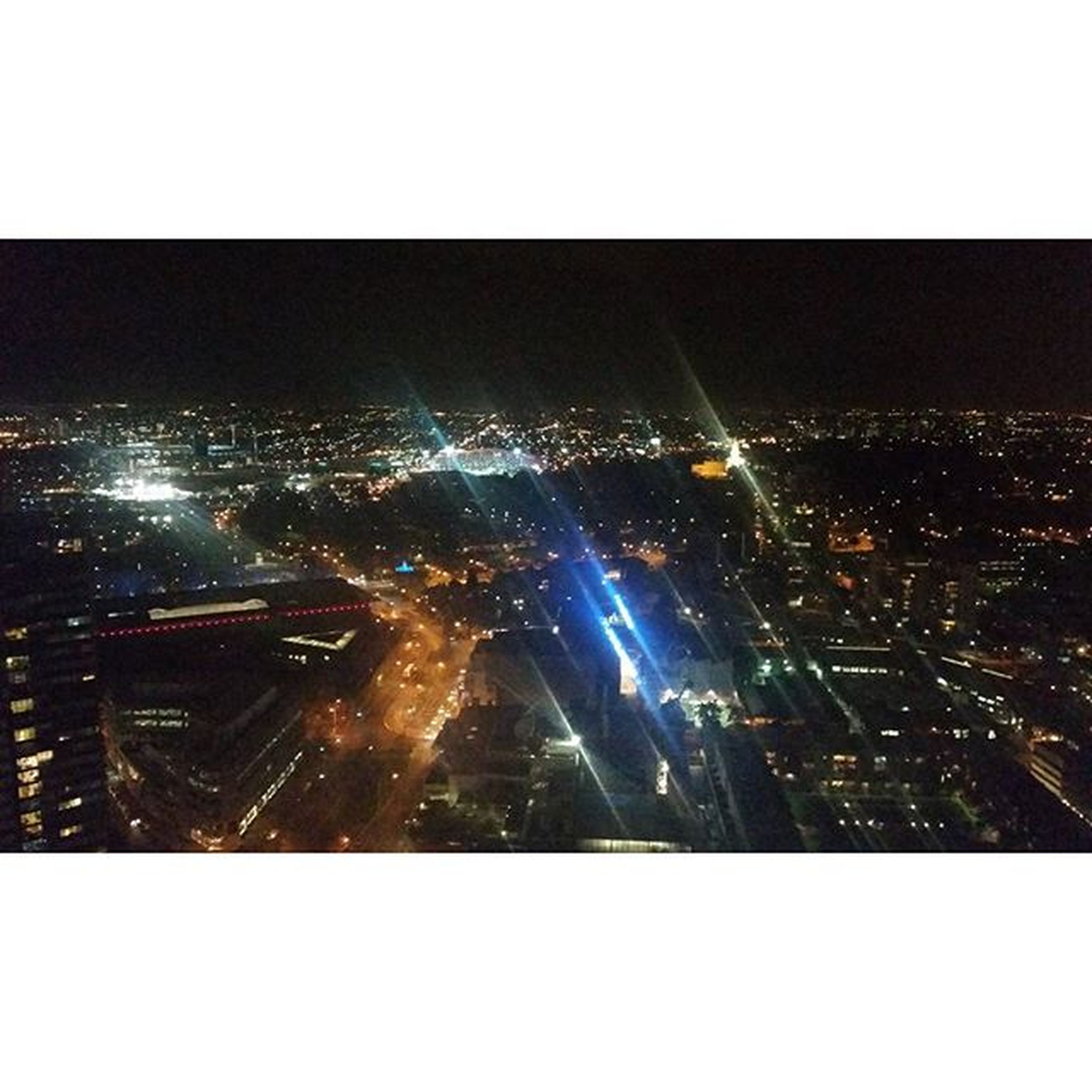 transfer print, illuminated, city, night, cityscape, auto post production filter, building exterior, architecture, built structure, city life, crowded, sky, skyscraper, high angle view, modern, clear sky, no people, outdoors, aerial view, light - natural phenomenon