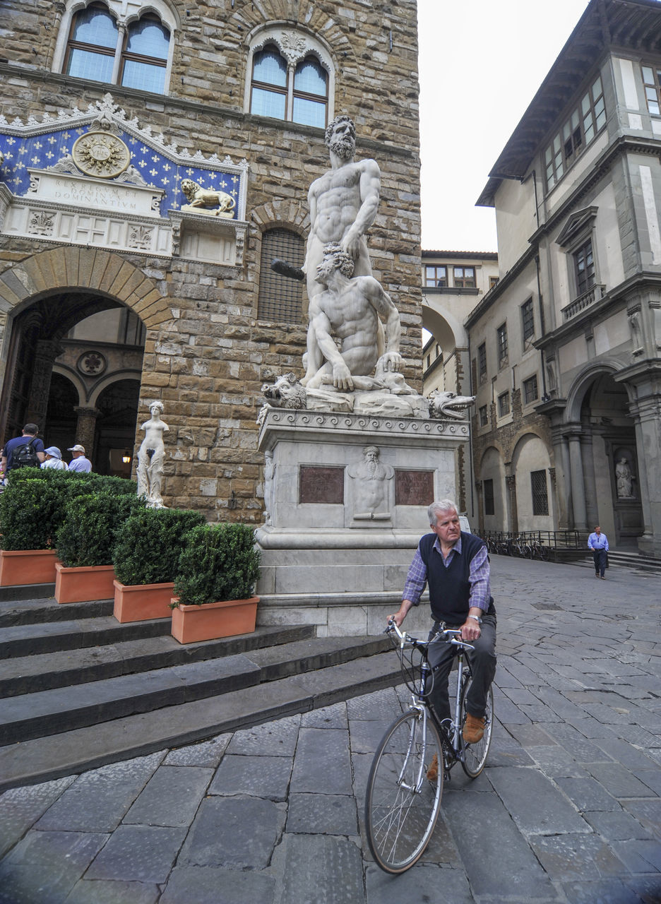 statue, sculpture, art and craft, building exterior, architecture, built structure, bicycle, human representation, real people, outdoors, travel, travel destinations, men, day, lifestyles, city, one person, people