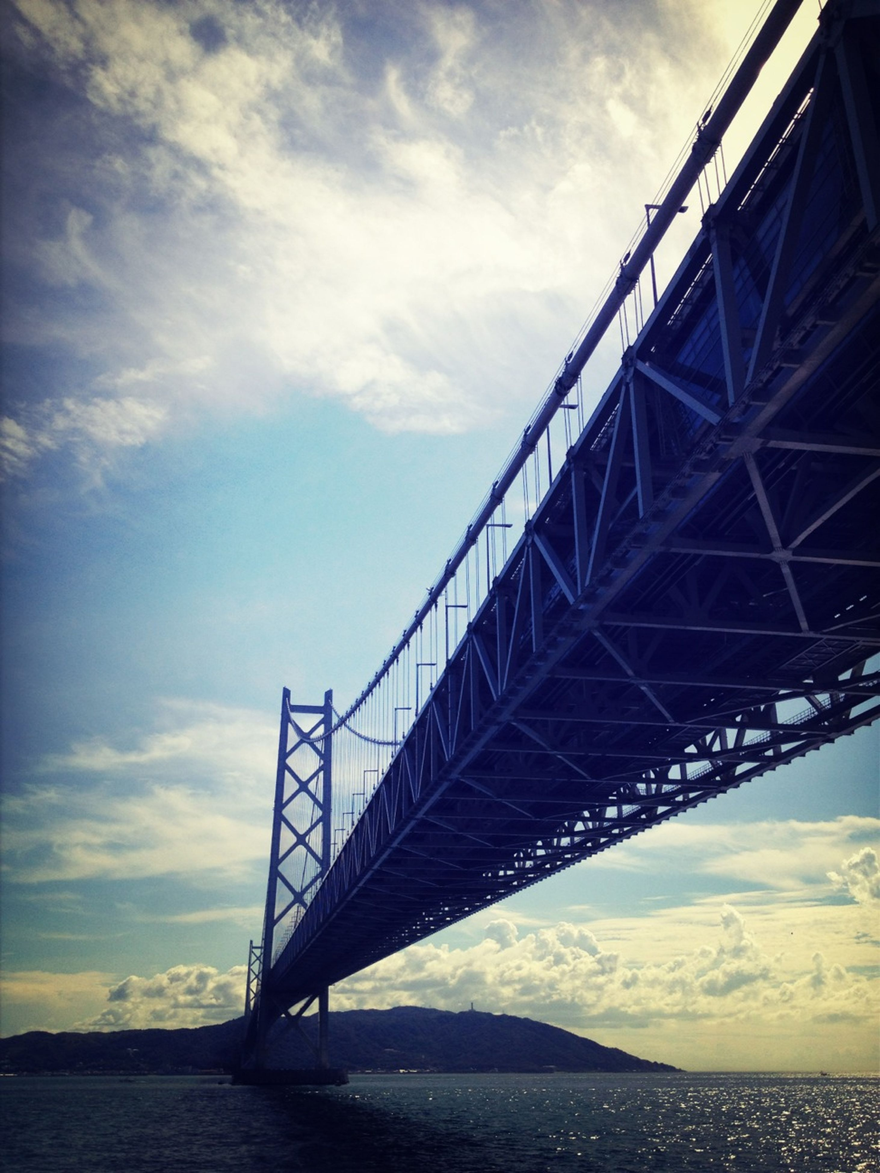 connection, engineering, built structure, bridge - man made structure, water, architecture, suspension bridge, sky, sea, bridge, low angle view, long, transportation, cloud - sky, waterfront, cloud, travel destinations, river, outdoors, no people