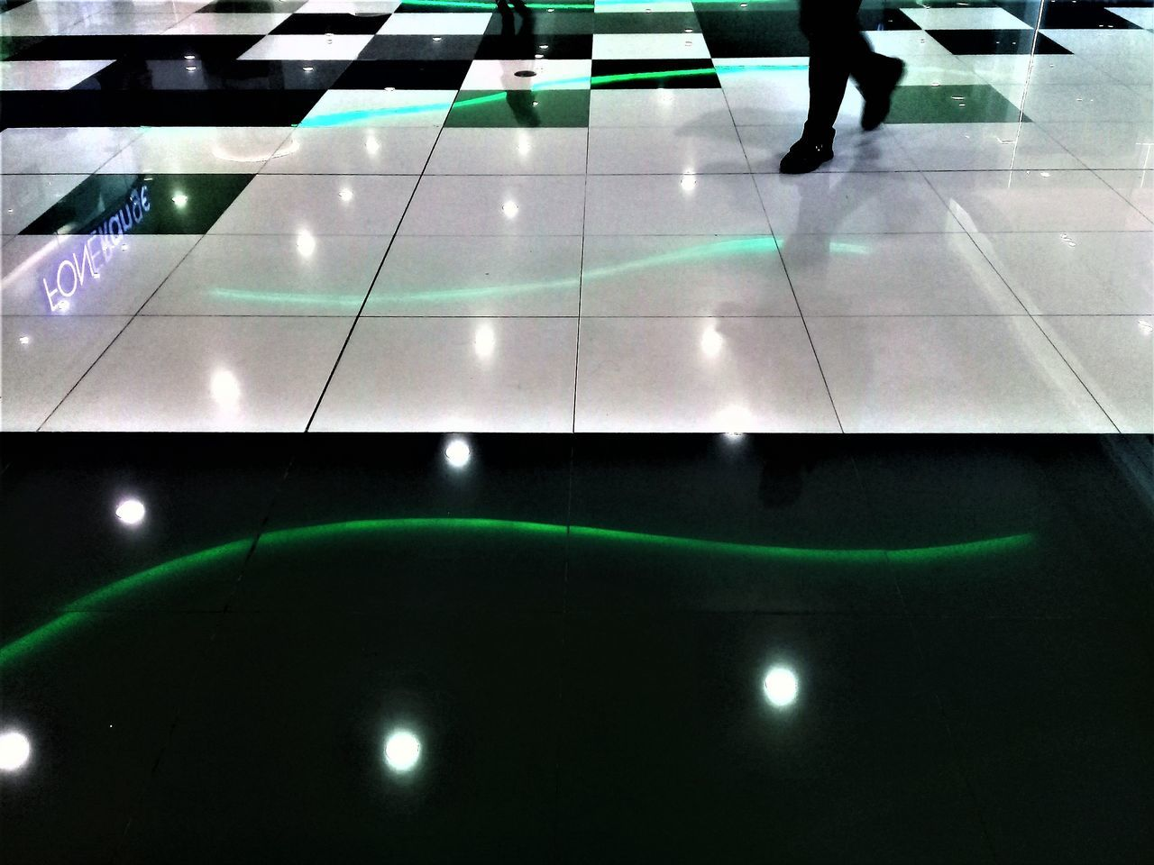 indoors, reflection, real people, low section, night, green color, illuminated, one person, human leg, lifestyles, people