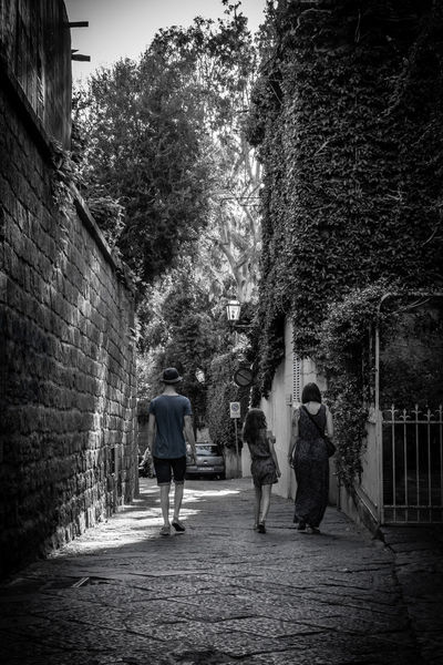 Architecture Building Exterior Built Structure Casual Clothing Day Family Footpath Friendship Leisure Activity Narrow Narrow Street Path Pathway Person Togetherness Tree Walking Walking Together Wall - Building Feature