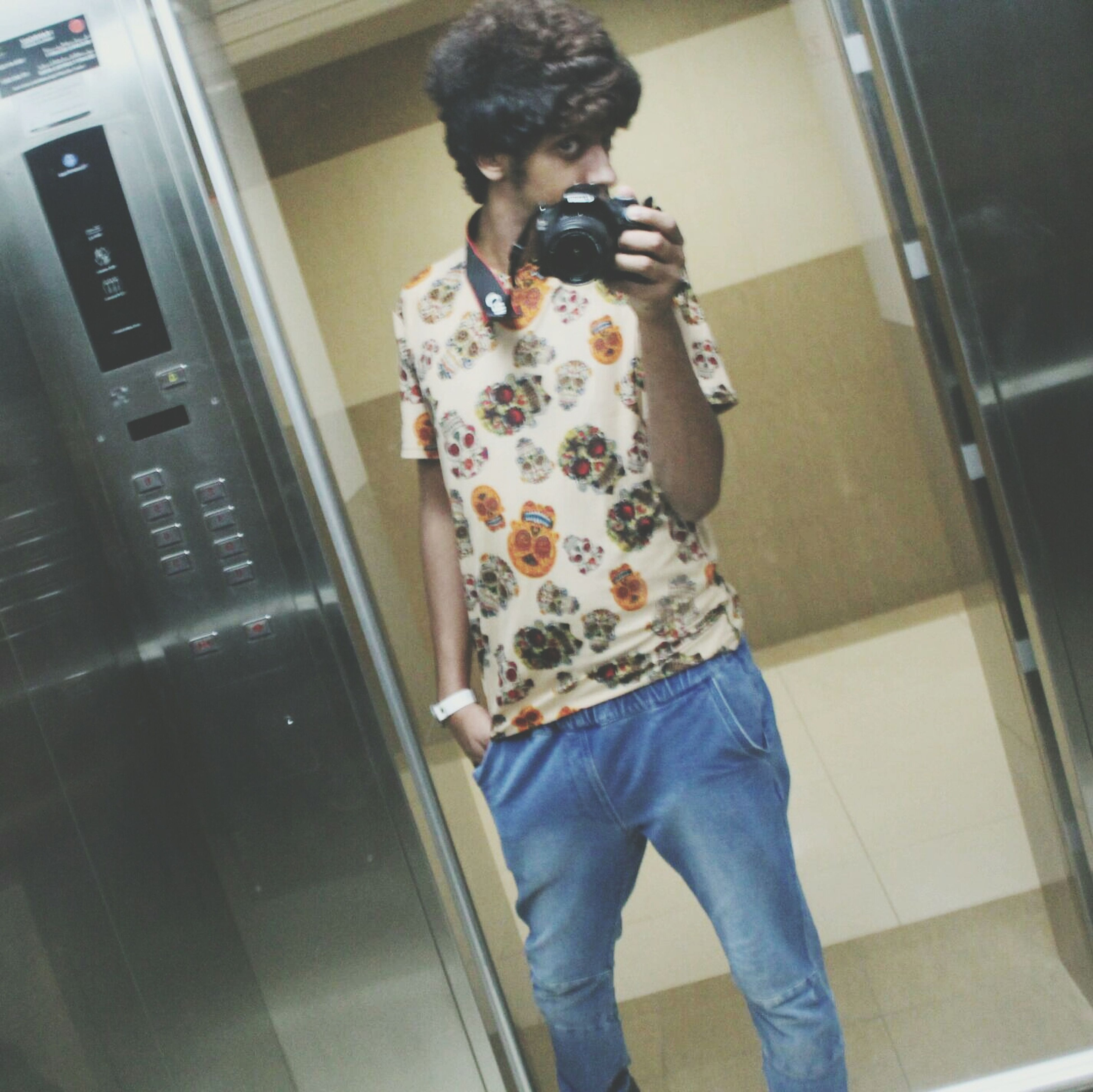 indoors, casual clothing, lifestyles, full length, person, three quarter length, leisure activity, standing, young adult, front view, technology, holding, home interior, wireless technology, architecture, portrait, looking at camera, young men