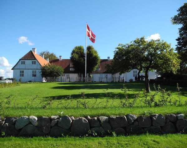 Tersløsegaard Museum in Tersløse on the island of Zealand in Denmark - Flag Architecture Identity Tree National Flag Building Exterior Built Structure Patriotism Clear Sky Growth Green Color Field Formal Garden Tranquility Blue Pride Lawn Tranquil Scene Agriculture Day Tersløsegaard Museum Tersløse Zealand Denmark Danmark