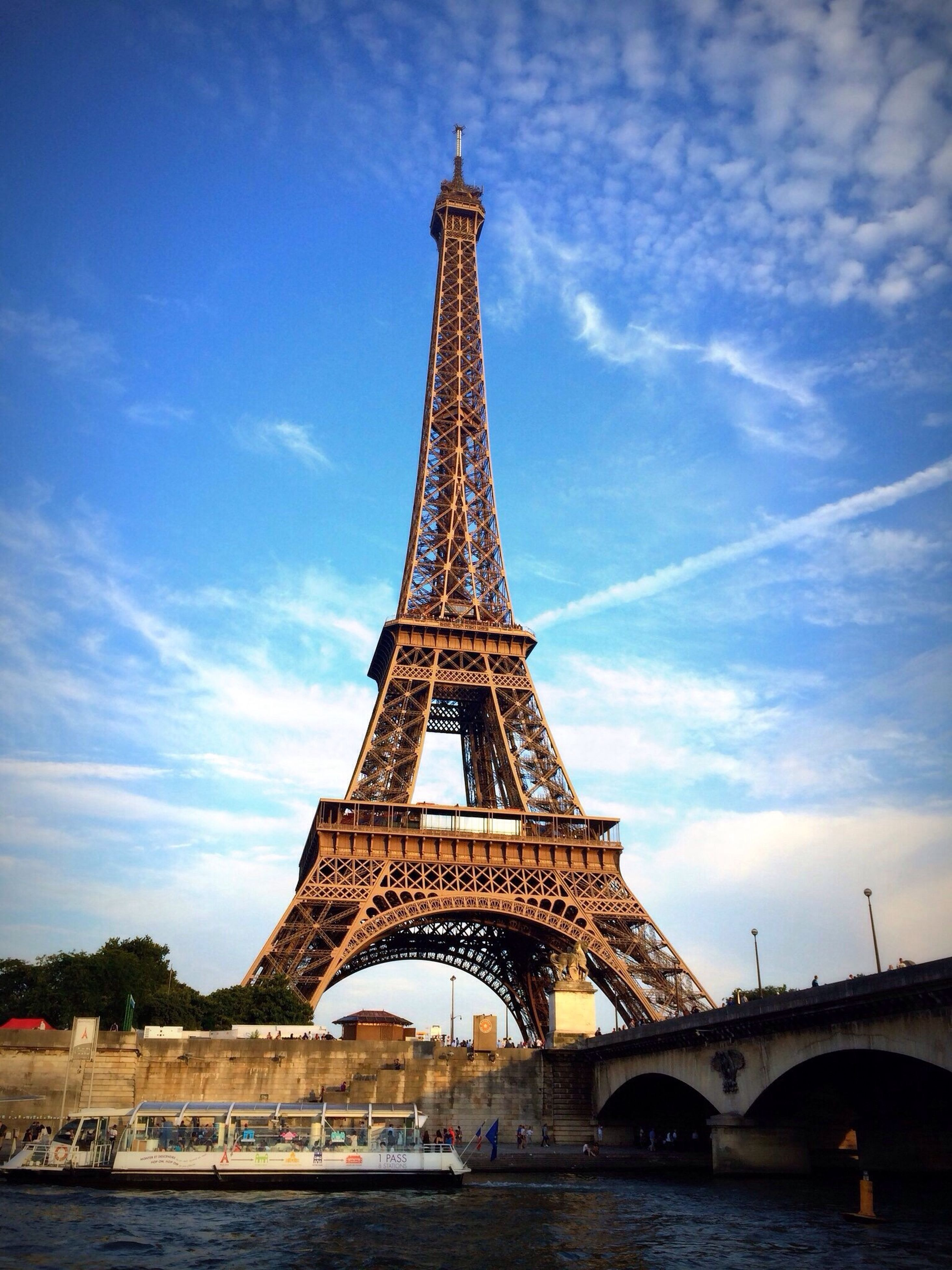 architecture, built structure, famous place, eiffel tower, international landmark, travel destinations, tourism, sky, travel, culture, capital cities, tower, water, history, cloud - sky, tall - high, metal, river, bridge - man made structure, low angle view