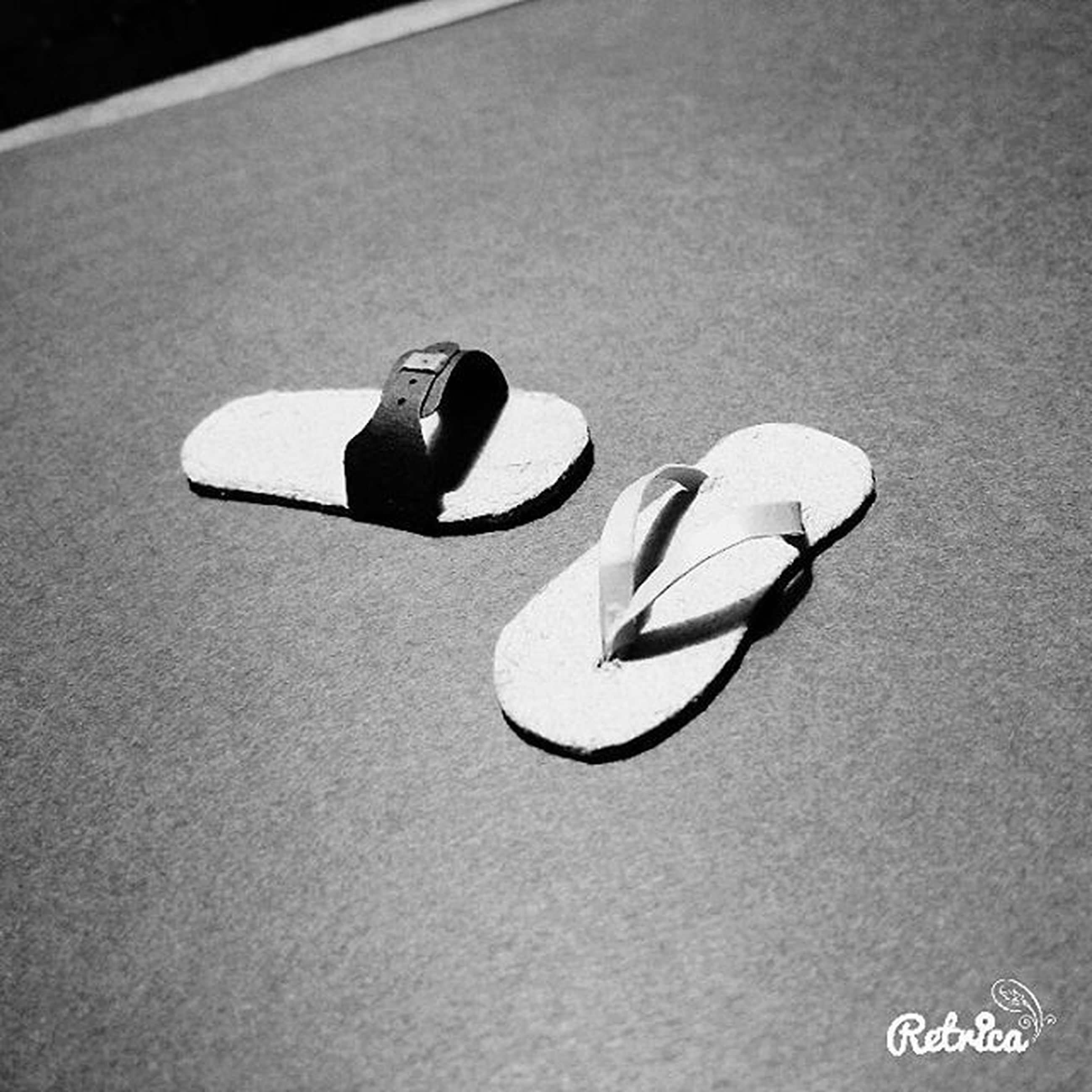 high angle view, shoe, still life, footwear, pair, close-up, indoors, shadow, single object, street, communication, day, two objects, no people, directly above, sunlight, absence, text, low section, black color