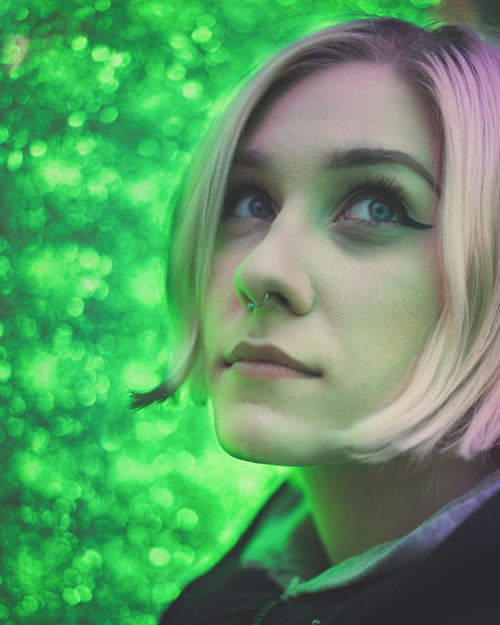 one person, serious, beautiful woman, young adult, close-up, real people, green color, young women, portrait, focus on foreground, blond hair, headshot, day, looking at camera, outdoors, tree, nature, adult, people
