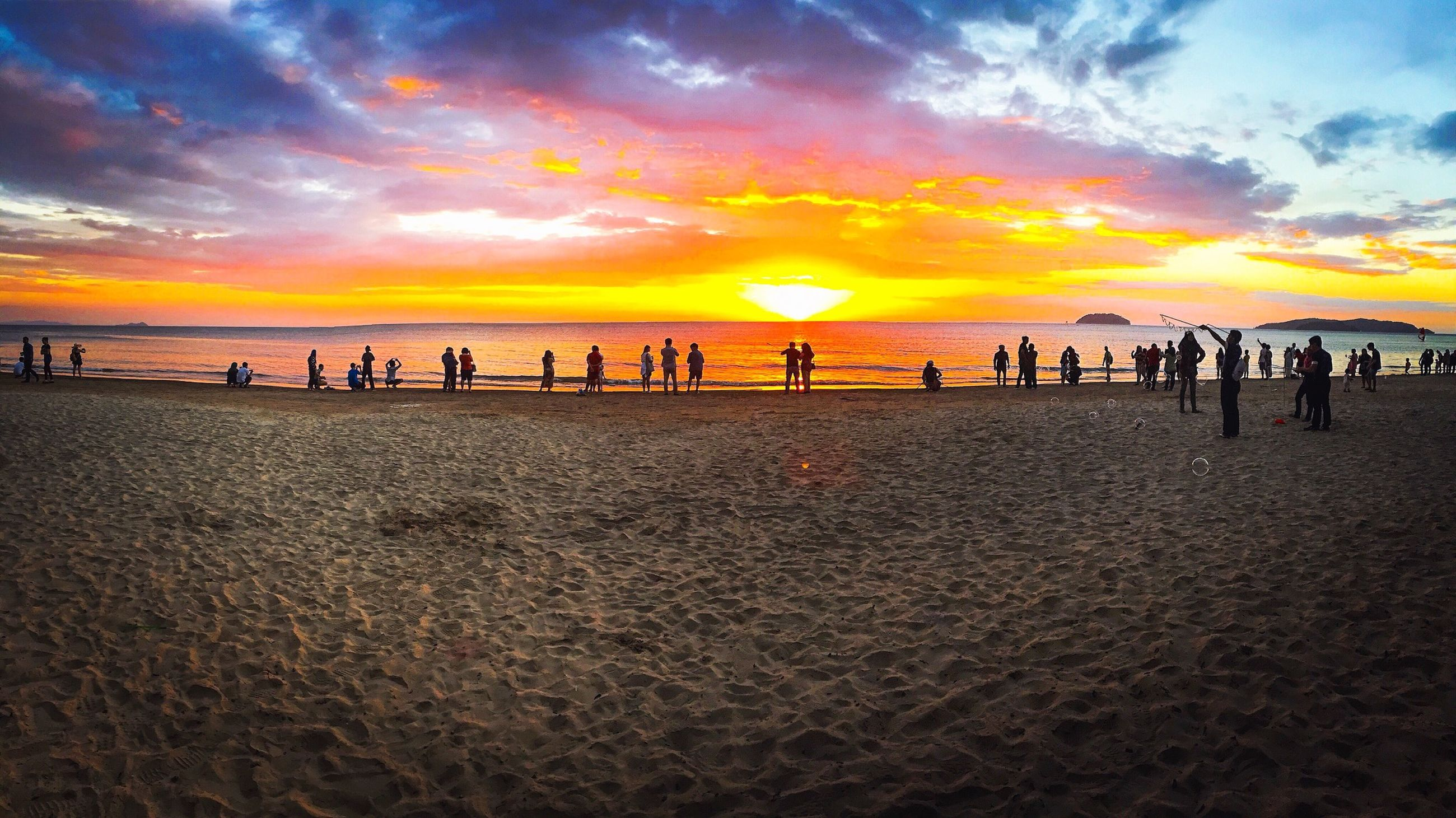 sea, sunset, beach, water, horizon over water, sky, scenics, beauty in nature, shore, tranquil scene, orange color, sand, tranquility, idyllic, cloud - sky, nature, vacations, large group of people, incidental people, tourism