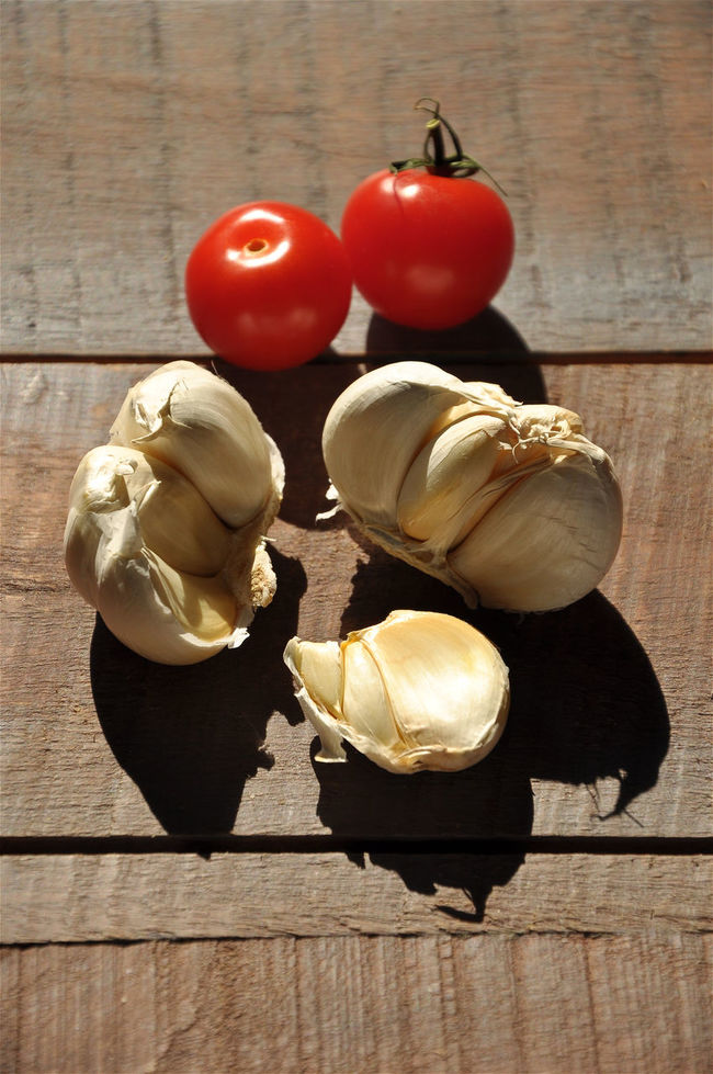 Tomatoes and garlic on wooden table Close-up Color Image Food Food And Drink Freshness Garlic Garlic Bulb Garlic Clove Indoors  No People Organic Red Ripe Still Life Table Tomato Vertical Wood - Material Wooden