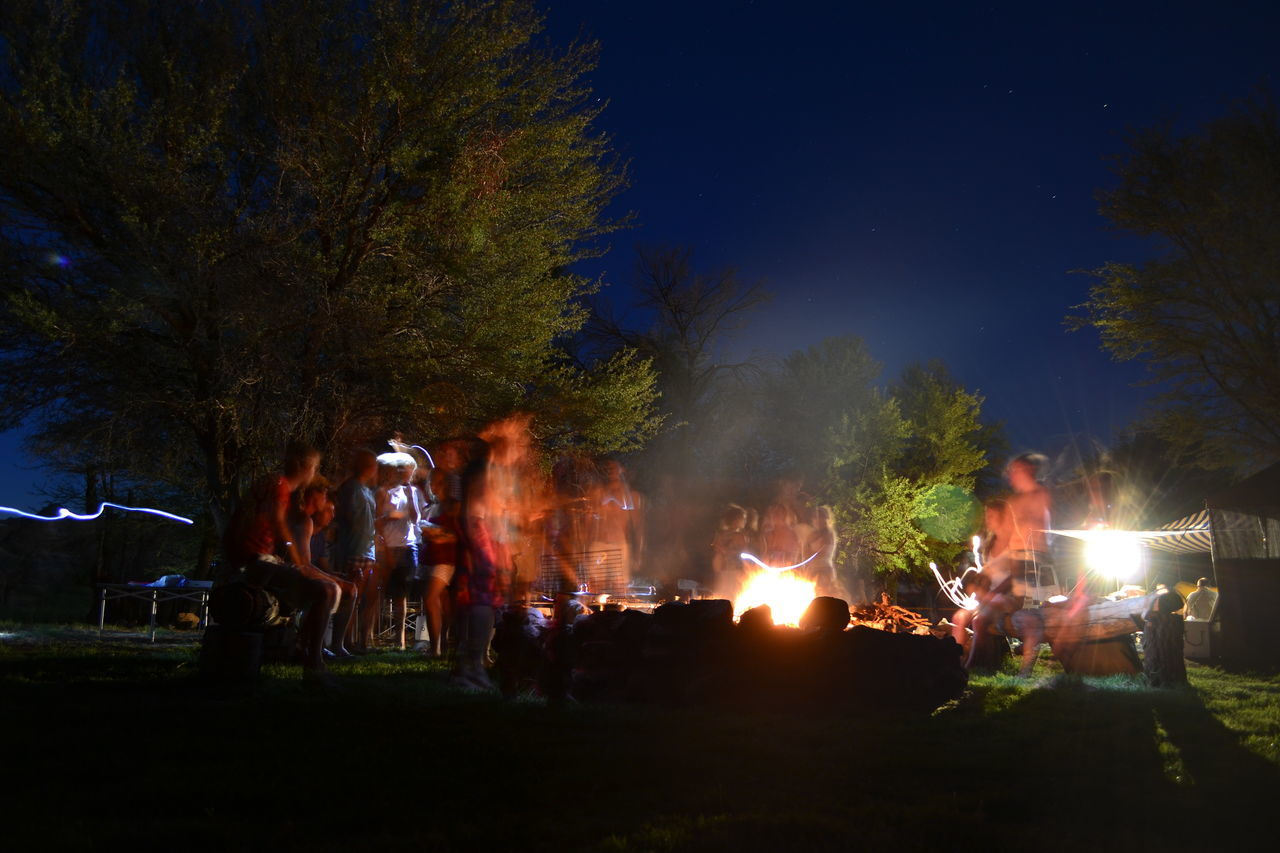 night, burning, real people, flame, outdoors, large group of people, illuminated, enjoyment, tree, nature, bonfire, sky, people