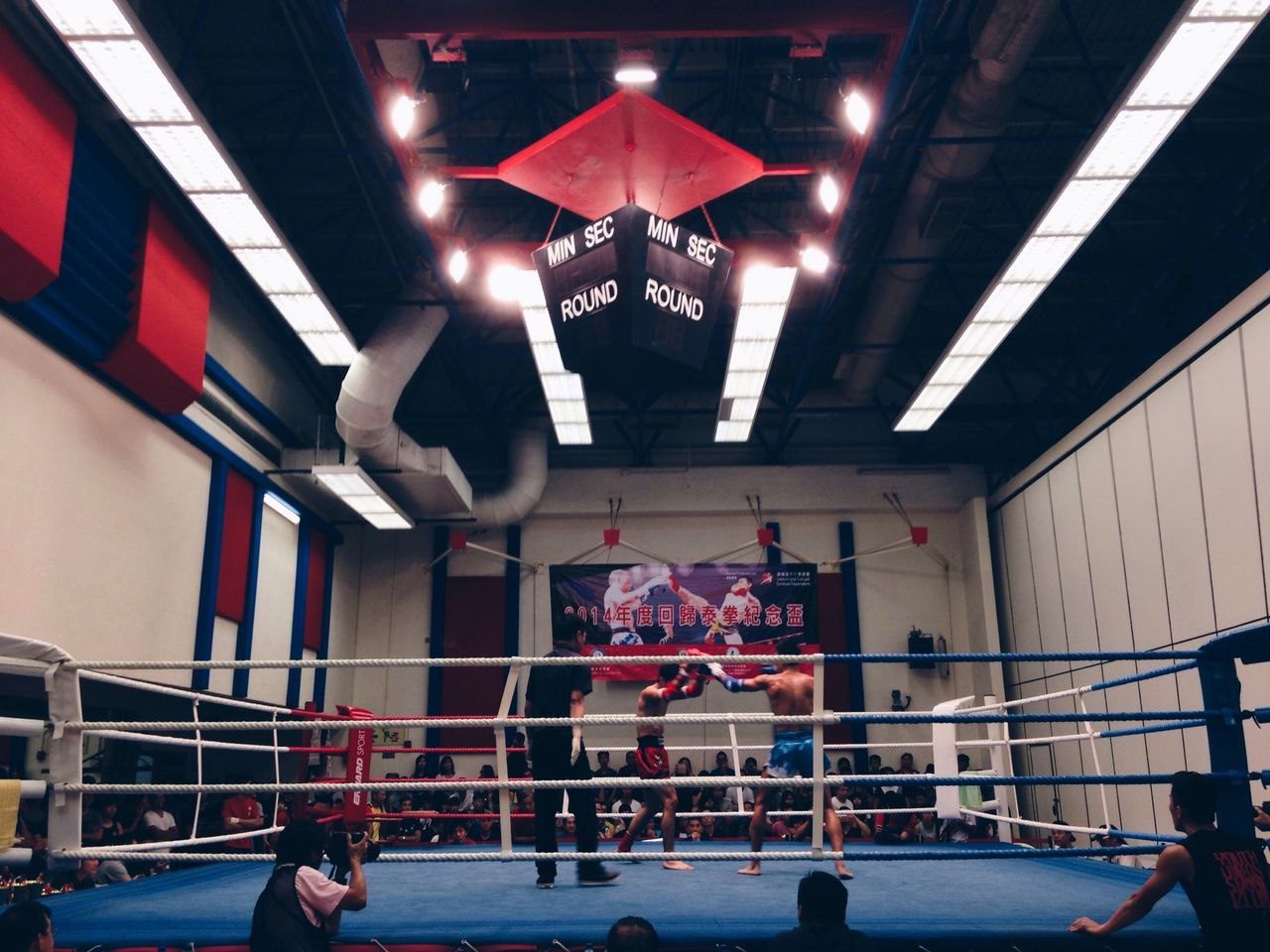 real people, men, indoors, sport, lifestyles, competition, illuminated, boxing ring, architecture, large group of people, built structure, group of people, women, sportsman, competitive sport, day, sports team, people