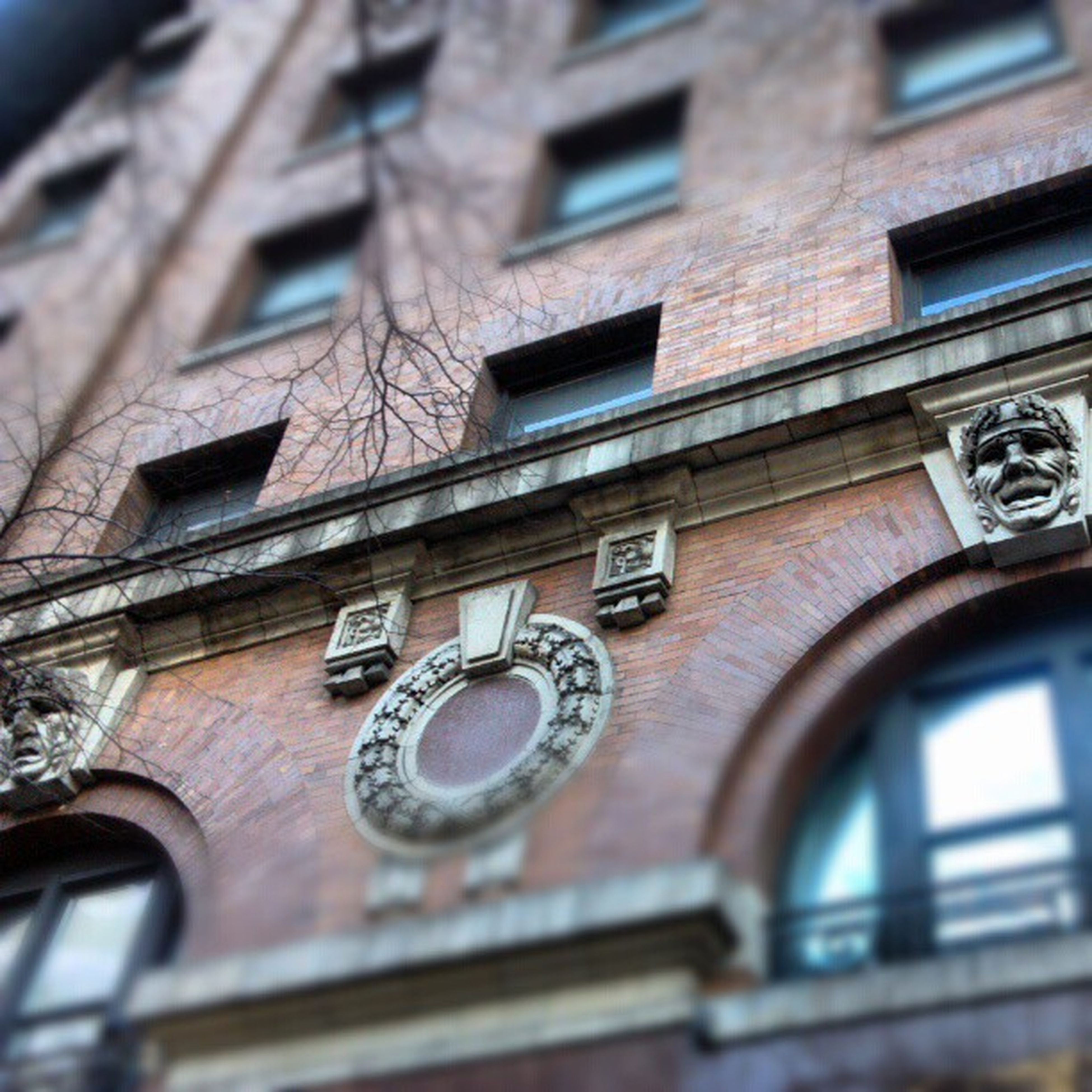 architecture, building exterior, built structure, low angle view, window, building, day, city, outdoors, residential building, close-up, no people, arch, residential structure, brick wall, focus on foreground, facade, time, part of, clock