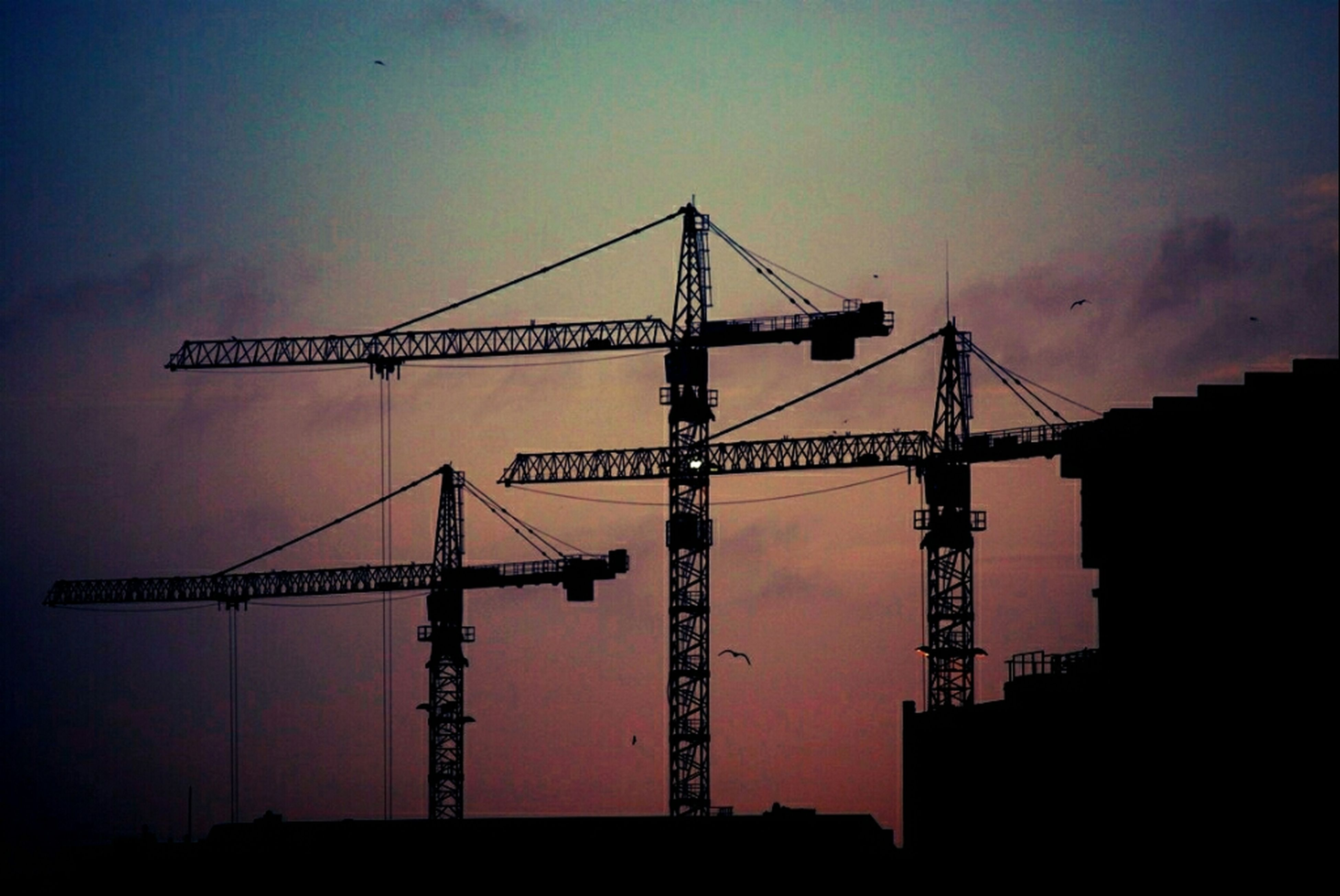 sunset, construction site, silhouette, built structure, architecture, crane, crane - construction machinery, development, construction, industry, building exterior, low angle view, clear sky, sky, copy space, incomplete, dusk, orange color, construction industry, outdoors