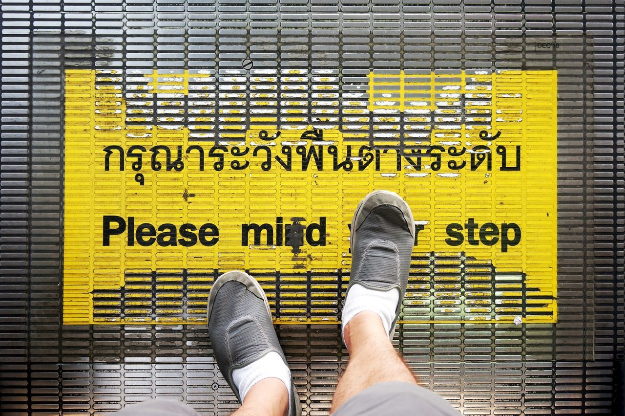 Low Section Of Man Standing On Metal Grate With Information Sign