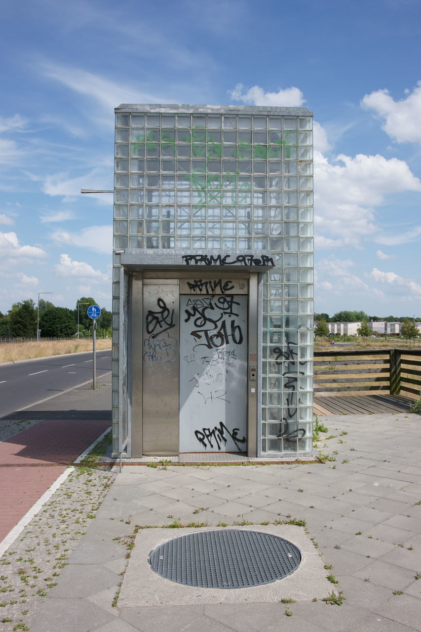 Graffiti On Glass Structure Against Sky