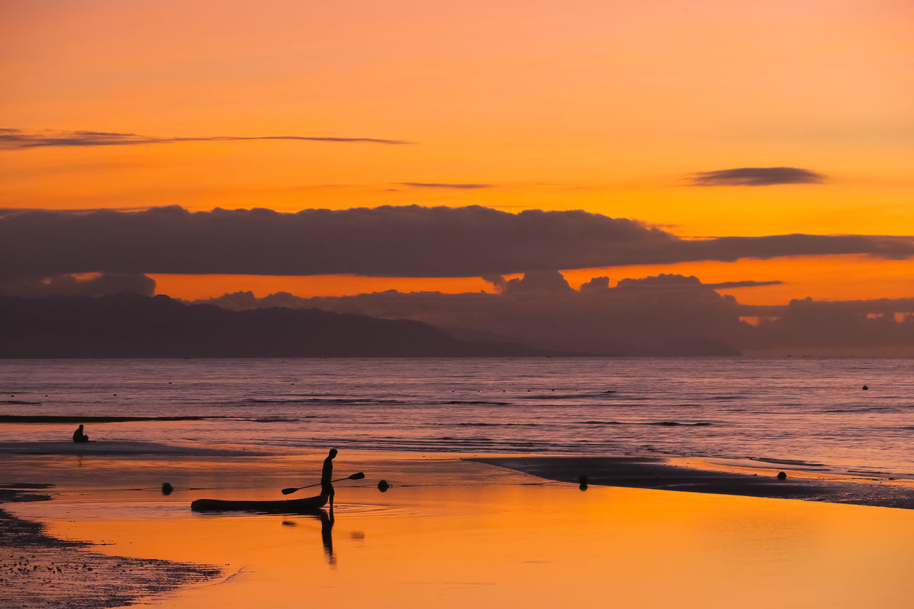 Silhouette of man dragging kayak out to sea during island sunrise Beach Beach Vacation Bohol Bohol Beach Club Fisherman Boat Idyllic Island Living Island Paradise Island Sunrise Island Sunset It's More Fun In The Philippines Kayak Kayaker Kayaking Man Silhouette Orange Color Orange Sky Sunset Orange Sun Orange Sunrise Orange Sunset Philippines Photos Reflection Serene Silhouette Of A Man Travel Destinations