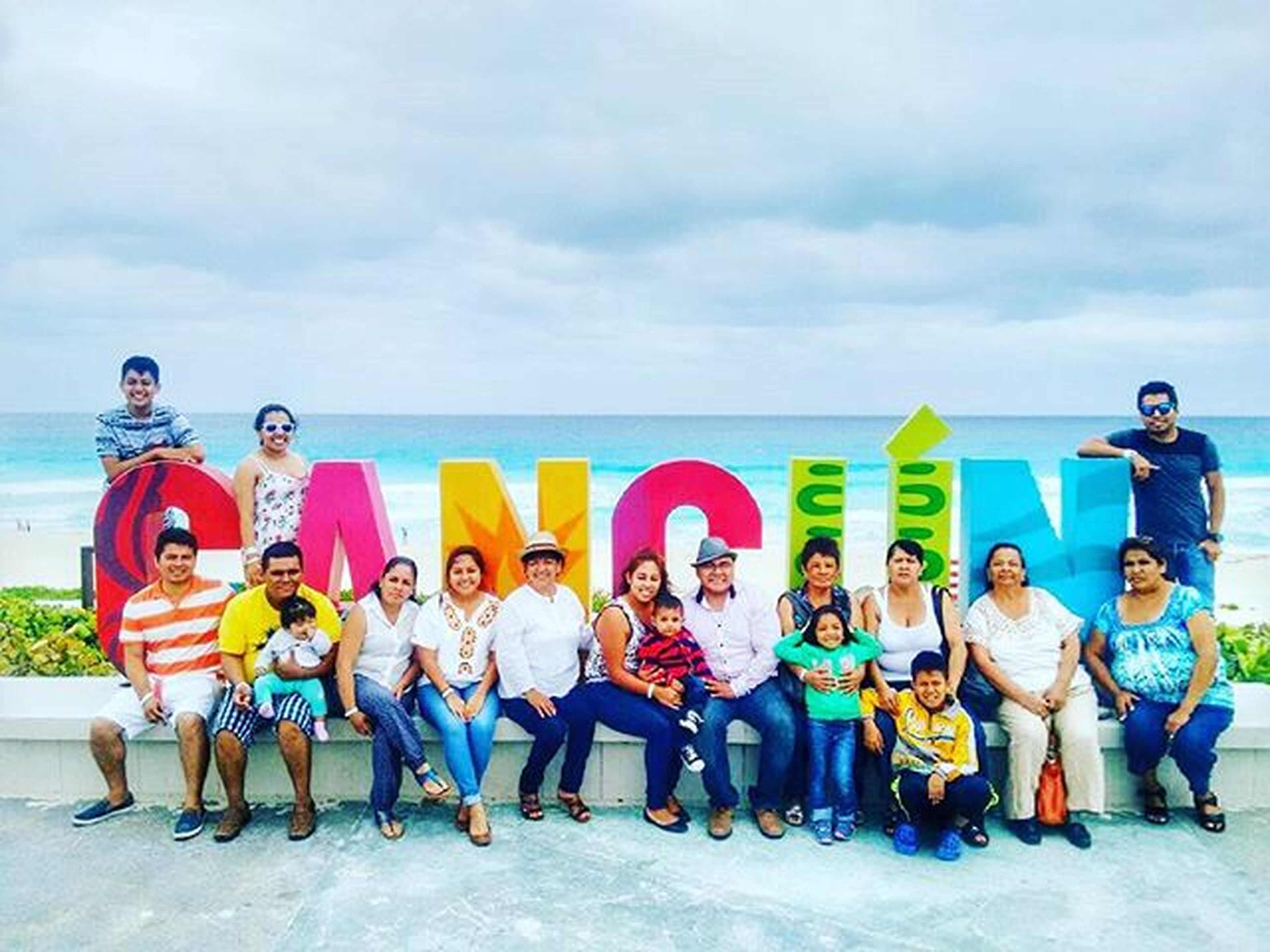 lifestyles, beach, leisure activity, sky, togetherness, childhood, sea, cloud - sky, shore, casual clothing, vacations, full length, boys, sand, bonding, girls, love, water, horizon over water