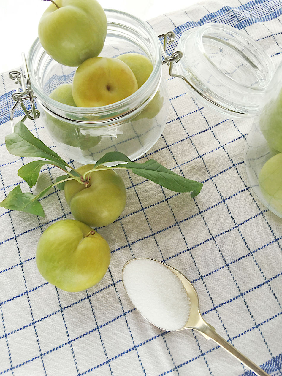 Green plums in jars with sugar Blue Close-up Day Dish Towel Foliage Food Preparation Fresh Fruit Glass Jars Green Color Green Plums Grid Harvest Healthy Eating Leaves Making Jam Natural Light No People Pattern Preserving Sugar Textures White