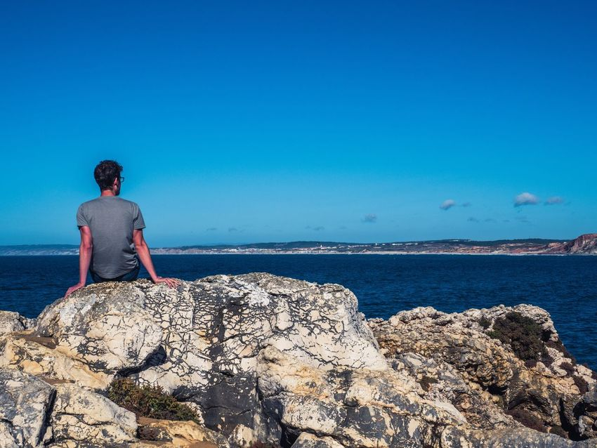 Man sitting on a rock and watches the coastline Rock - Object Real People One Person Blue Leisure Activity Lifestyles Sea Nature Rock Formation Clear Sky Water Full Length Scenics Young Adult Beauty In Nature Outdoors Day Horizon Over Water Sky Ocean View Man One Man Only Portugal Coastline Holiday Been There.