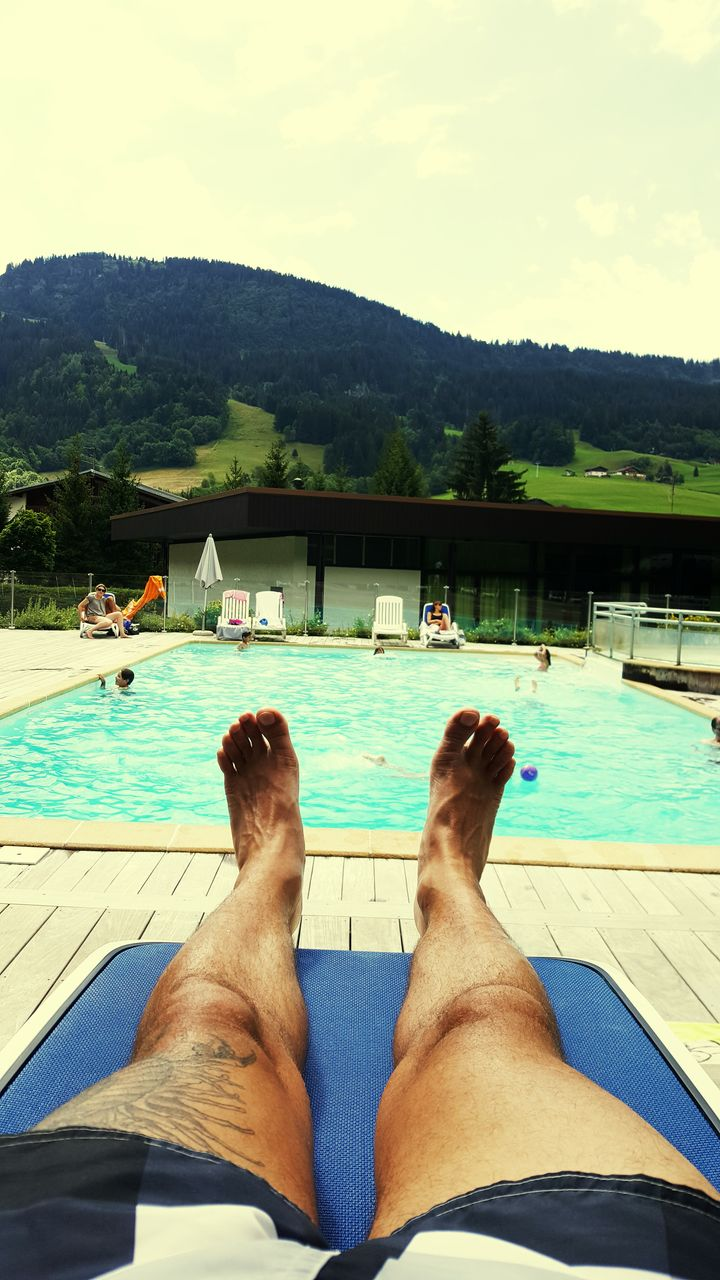 water, swimming pool, human leg, barefoot, one person, day, men, low section, human body part, outdoors, relaxation, nautical vessel, leisure activity, sky, lake, real people, nature, mountain, one man only, tree, people