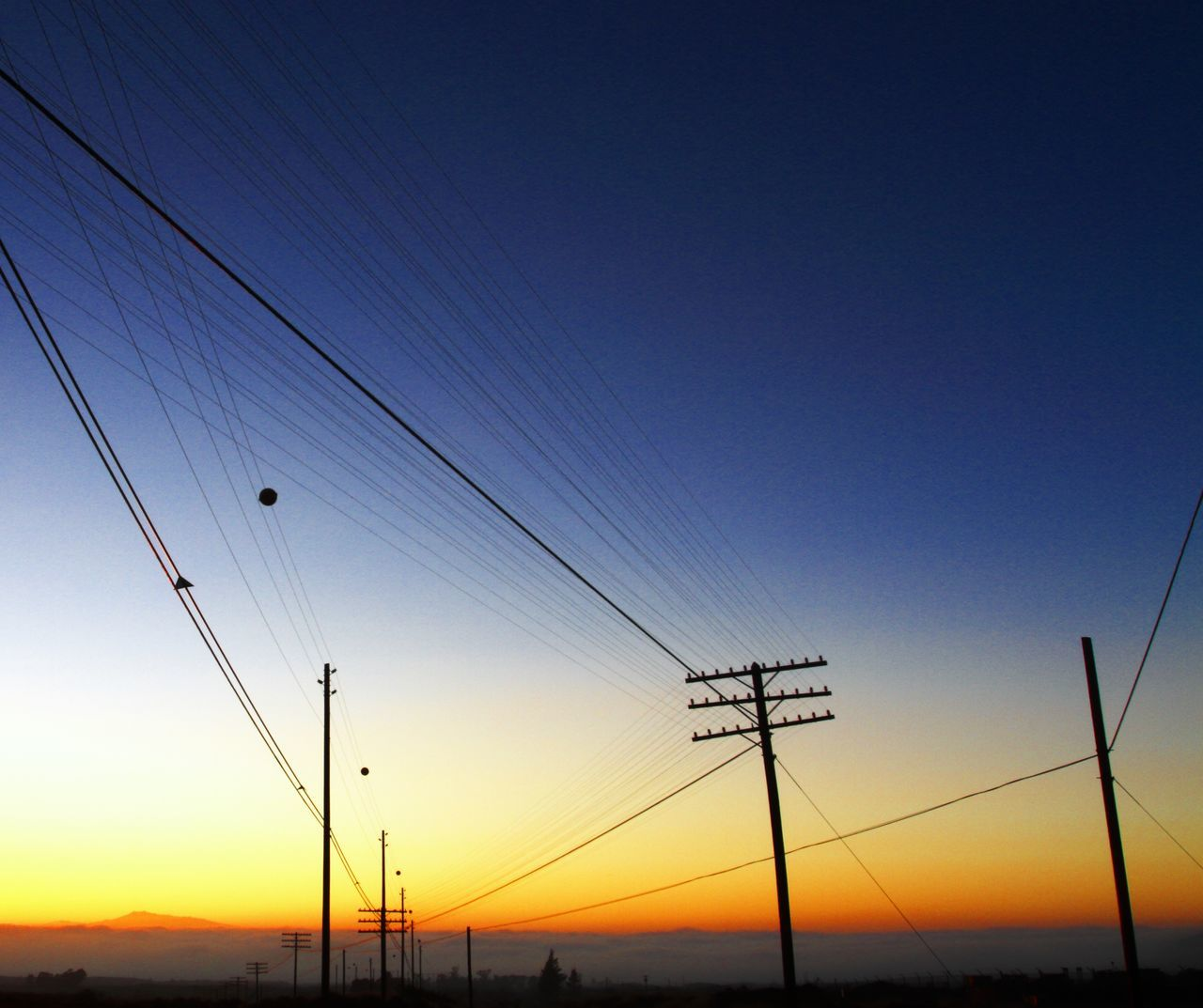 Low Angle View Of Silhouette Electricity Pylons Against Blue Sky During Sunset